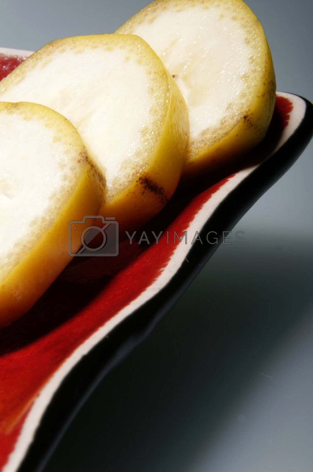 Slices of bananas on red plate