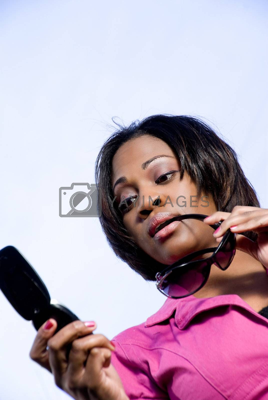 An African American woman reading a text message on the phone