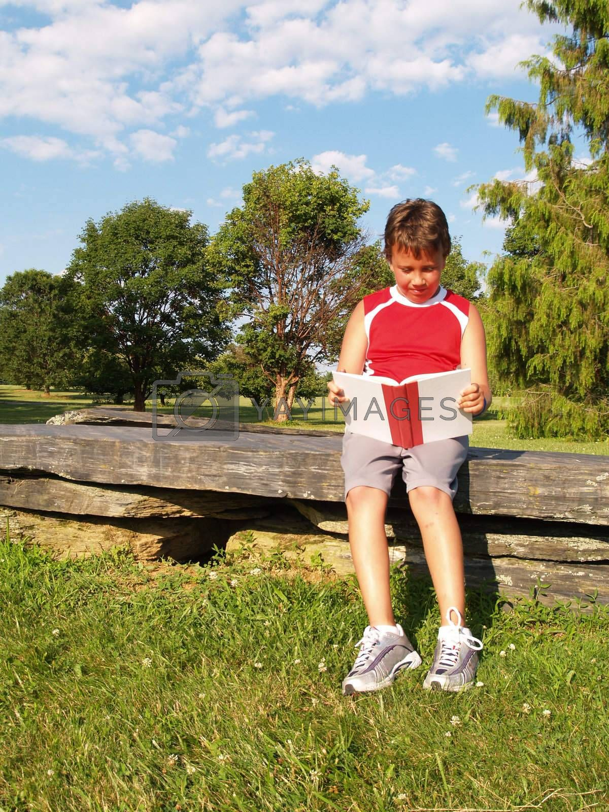 young boy reading a book in a park setting