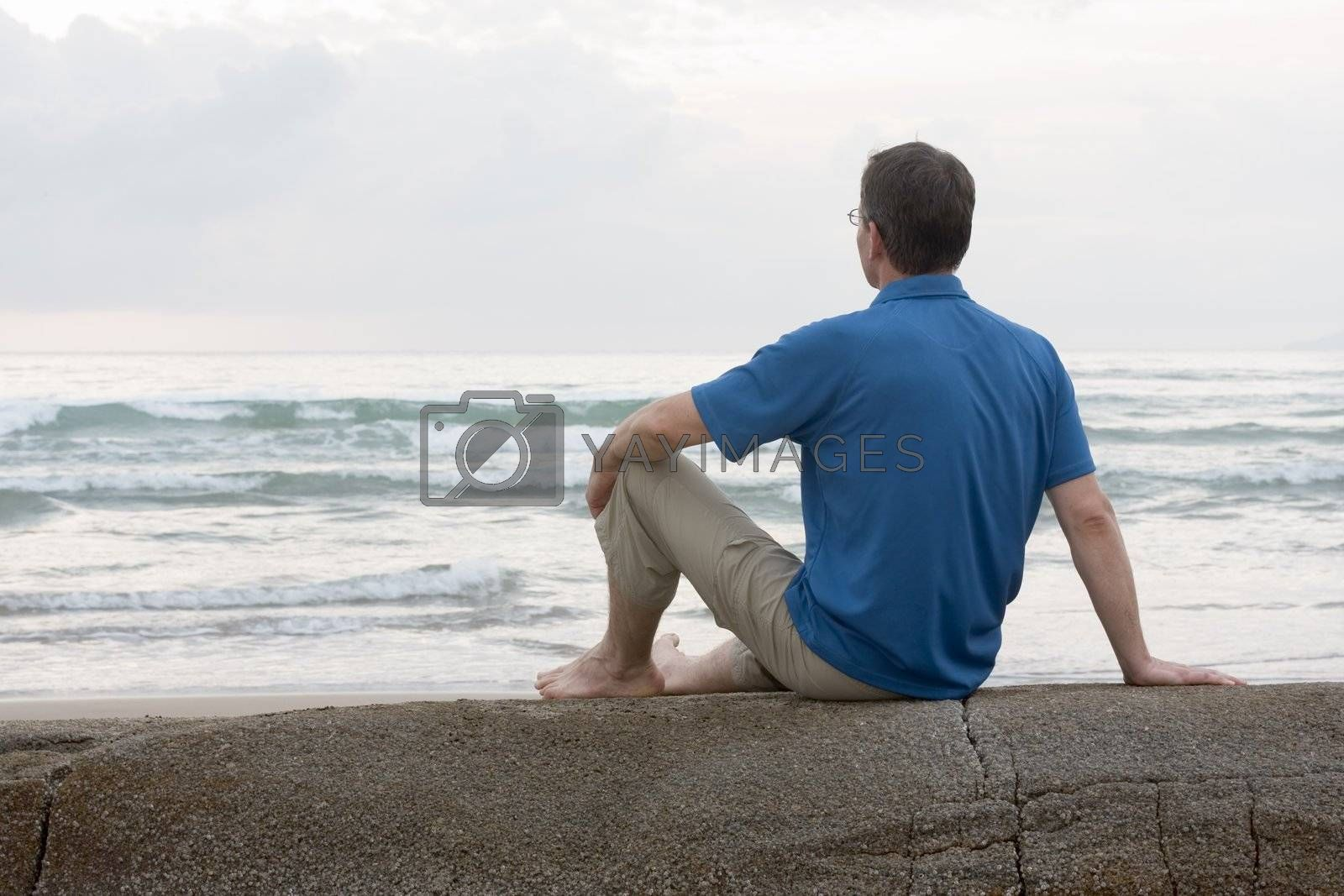 Royalty free image of Man sitting on a rock at the sea by ArtmannWitte