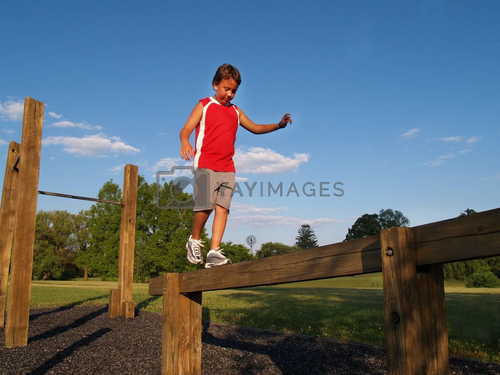 young boy balancing on a balance beam
