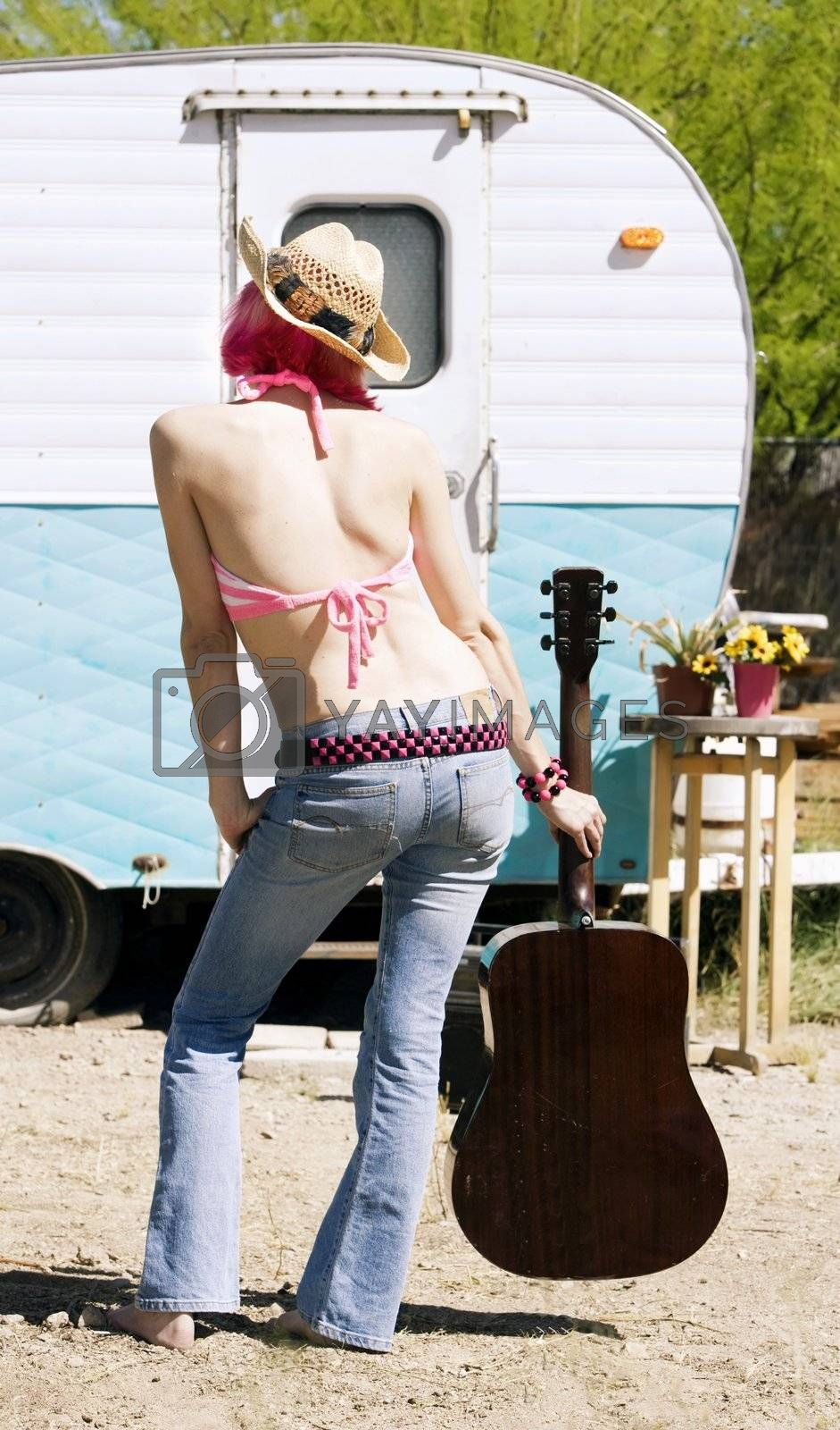 Pretty Woman Front of Vintage Travel Trailer with a Guitar