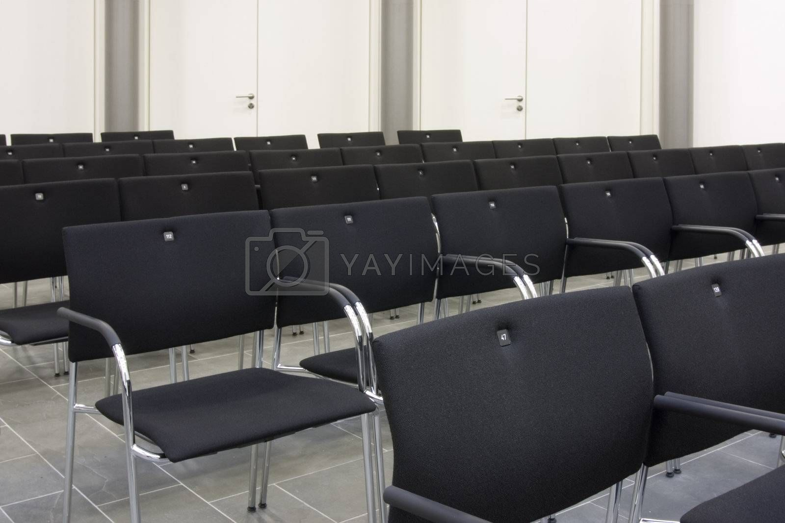 Black chairs of a lecture hall in a row