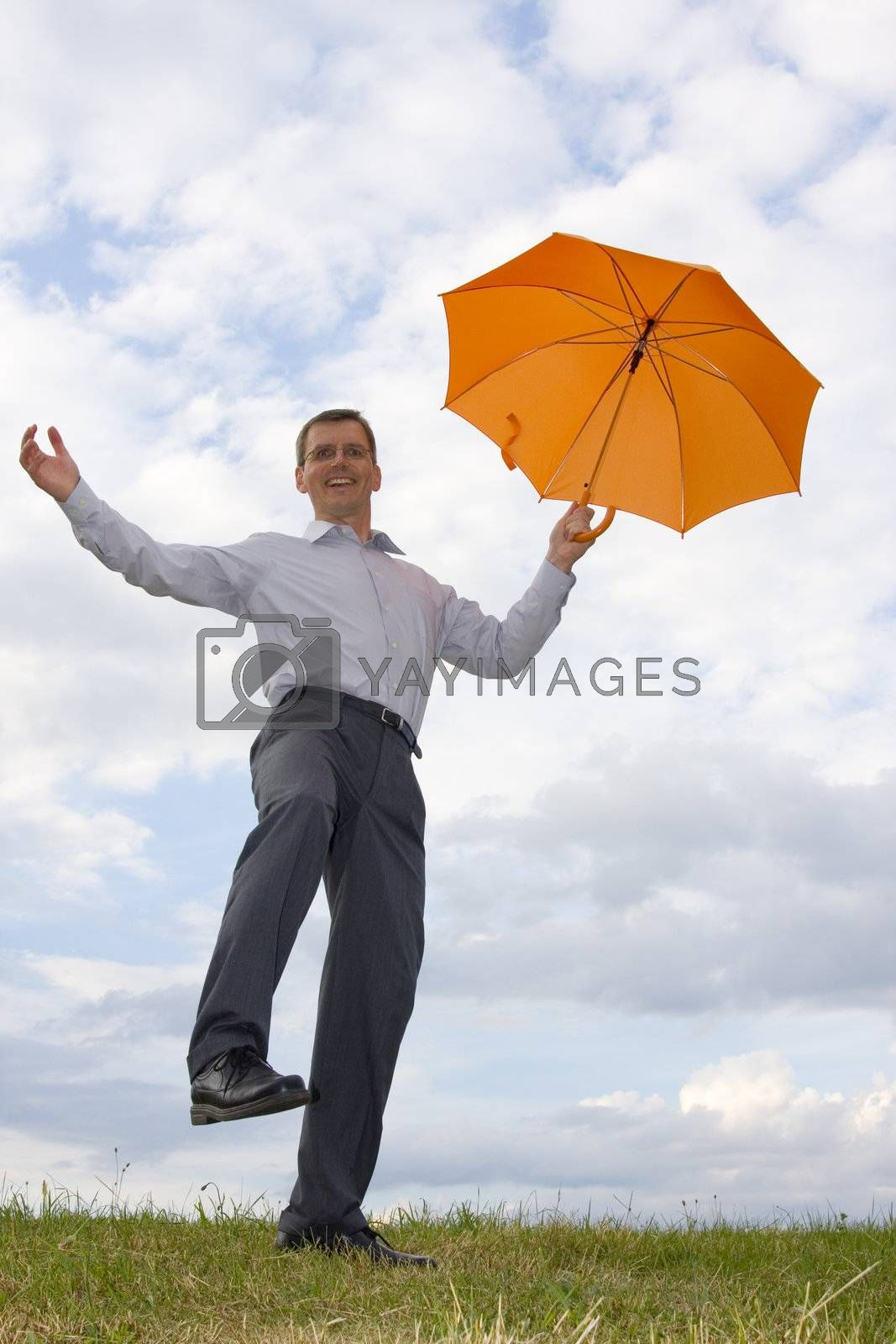 Happy laughing businessman with orange umbrella in a meadow