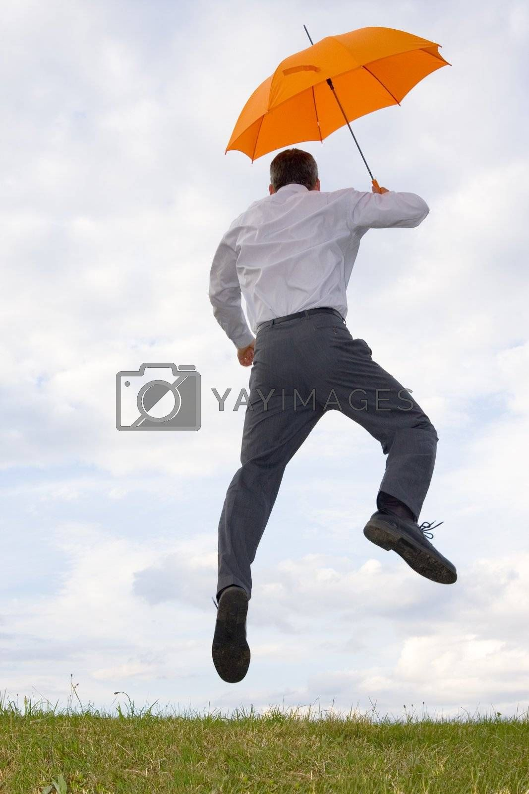 Happy businessman with orange umbrella jumping in a meadow
