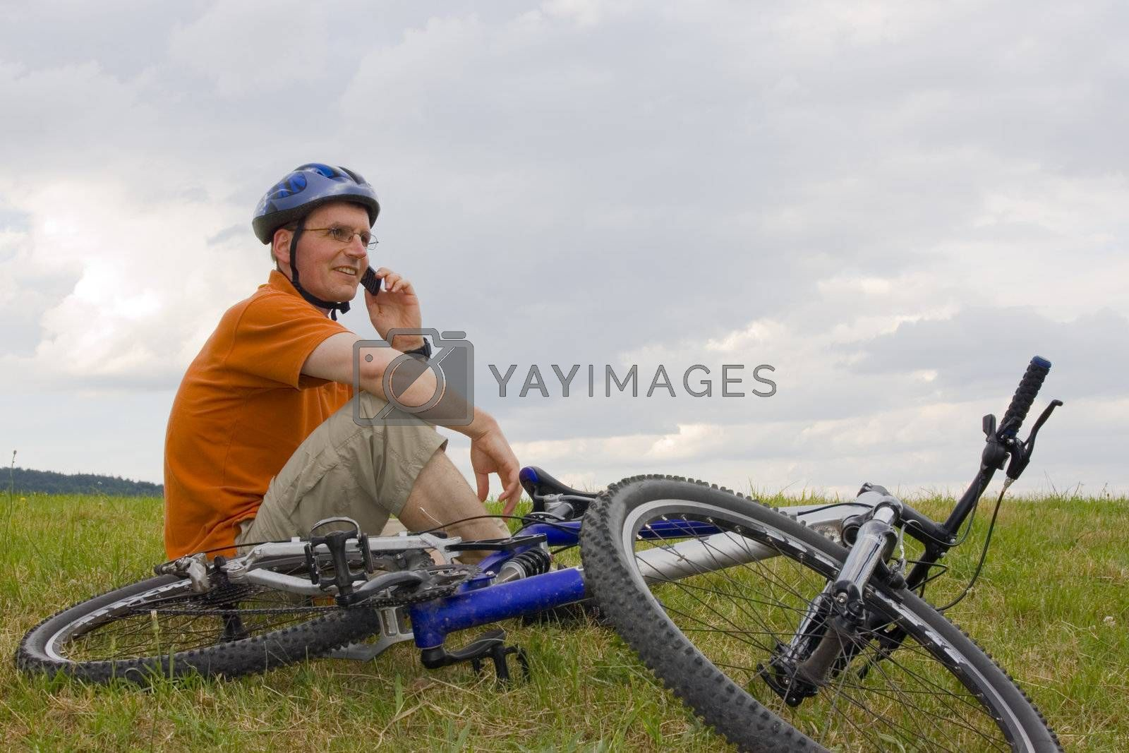 Royalty free image of Man with mountain bike talking on cell phone by ArtmannWitte