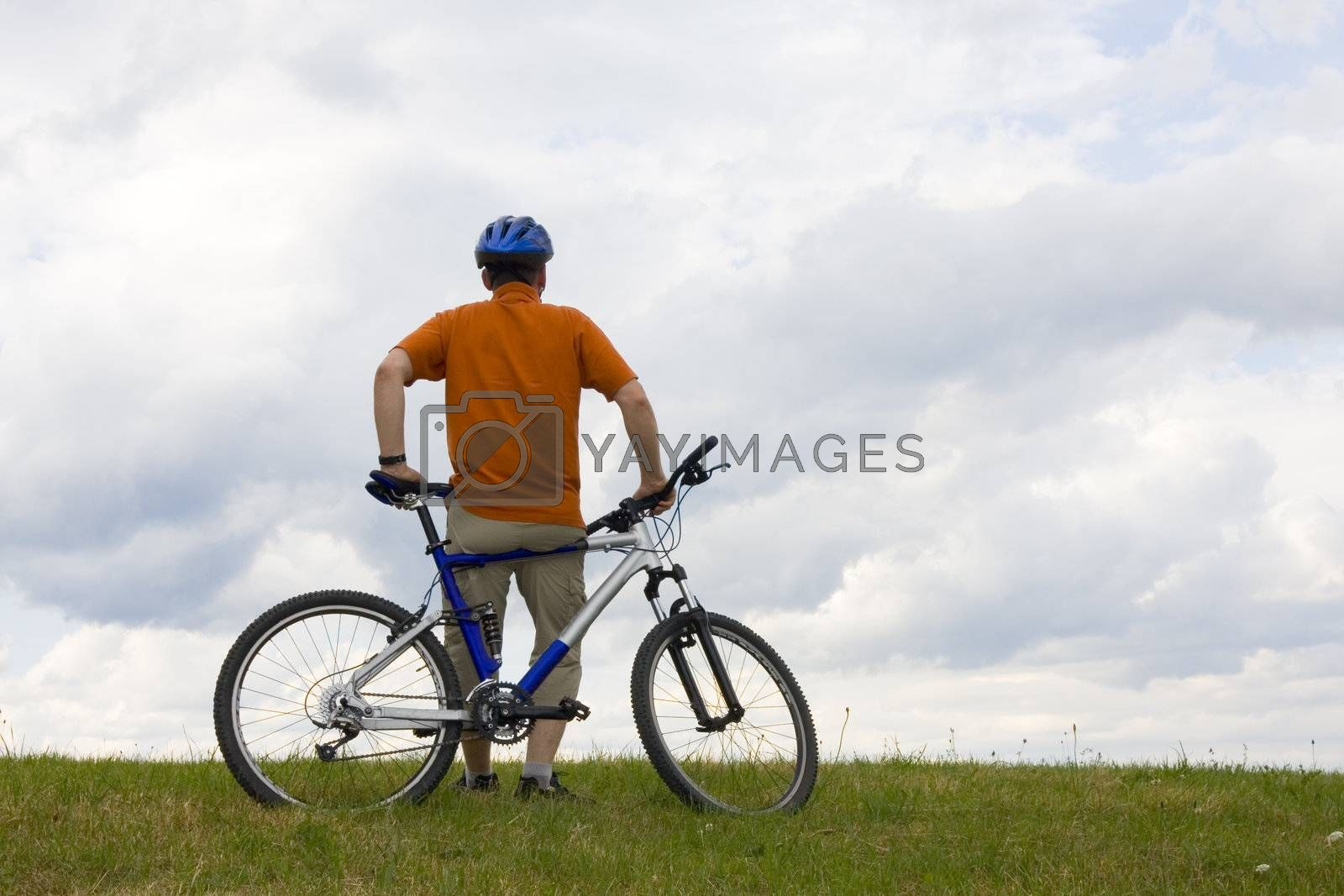 Man standing by his mountain bike in a meadow