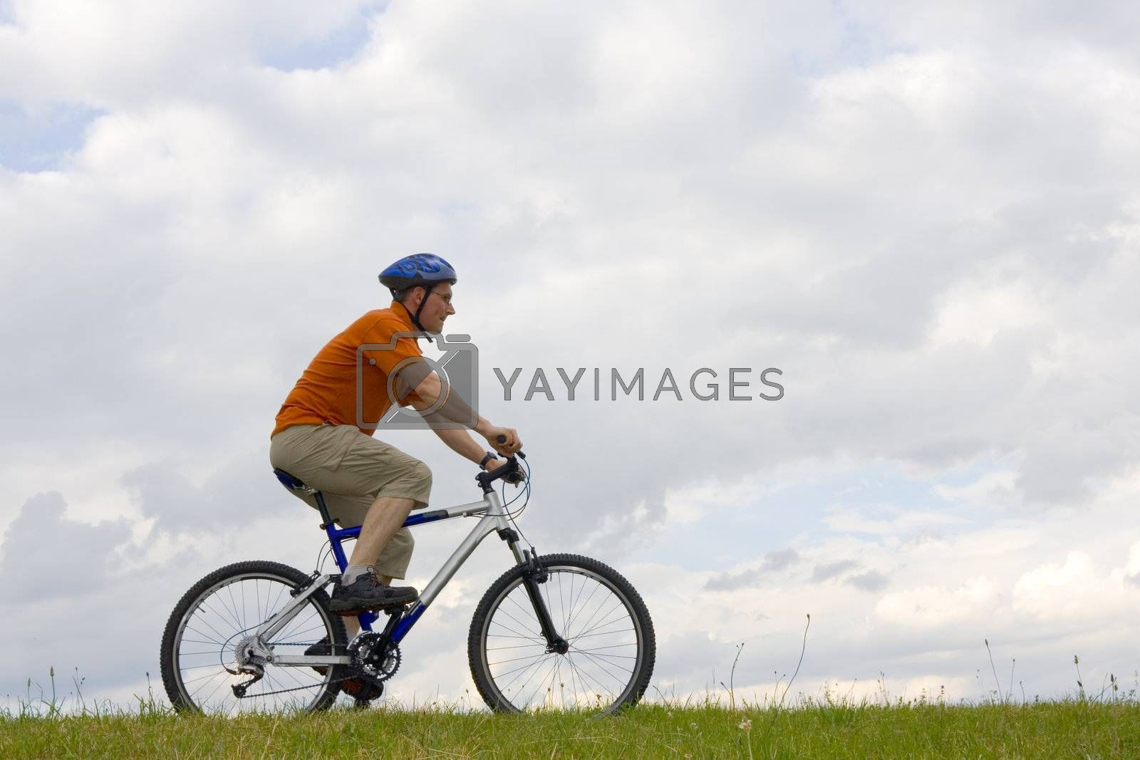 Man riding a mountain bike in a meadow against cloudy sky