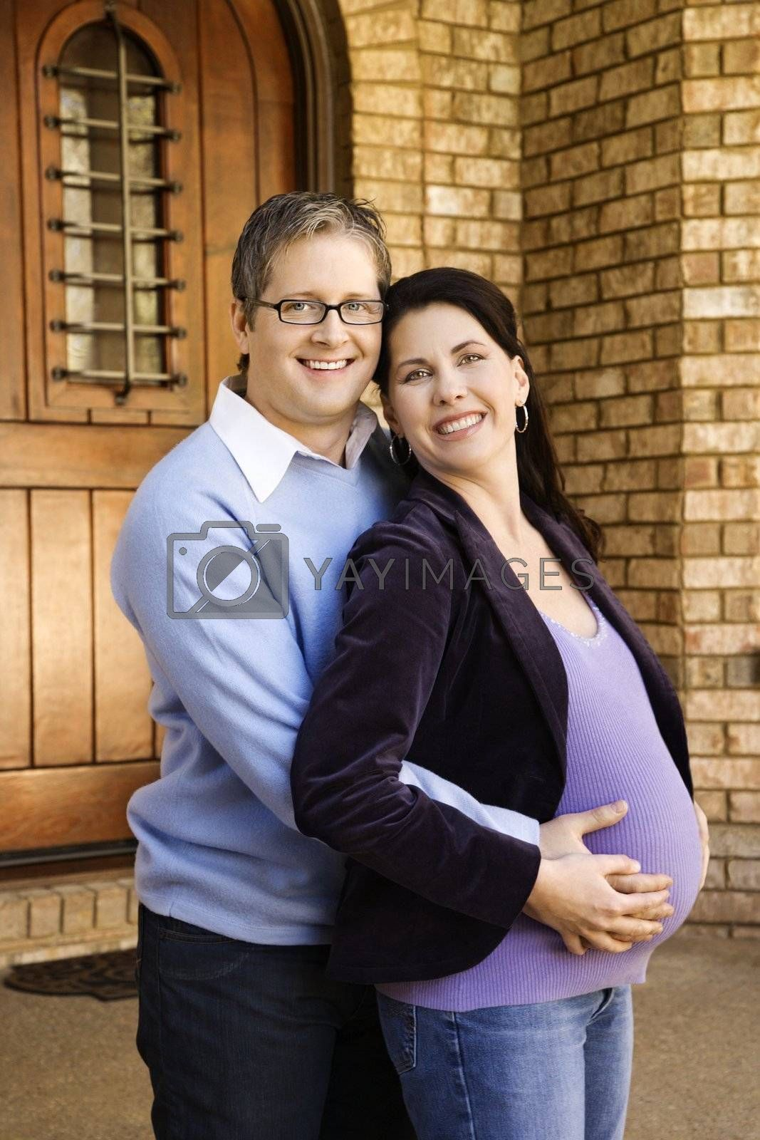 Portrait of adult male and pregnant female embracing near doorway.