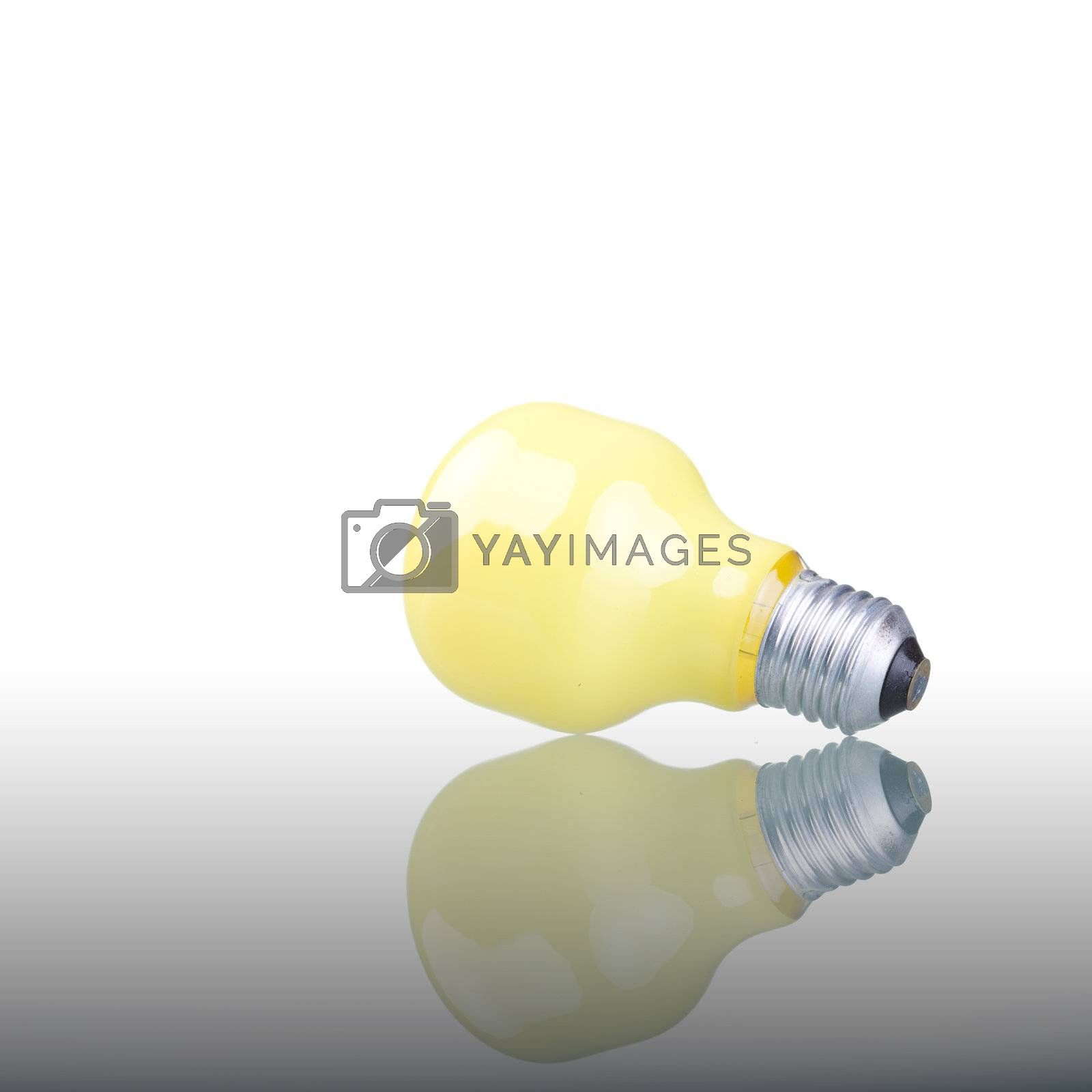 Yellow lightbulb with reflection on glass surface.