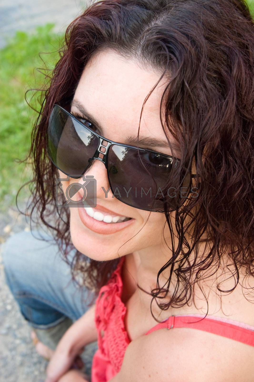 Young woman wearing sunglasses, with a wide smile.