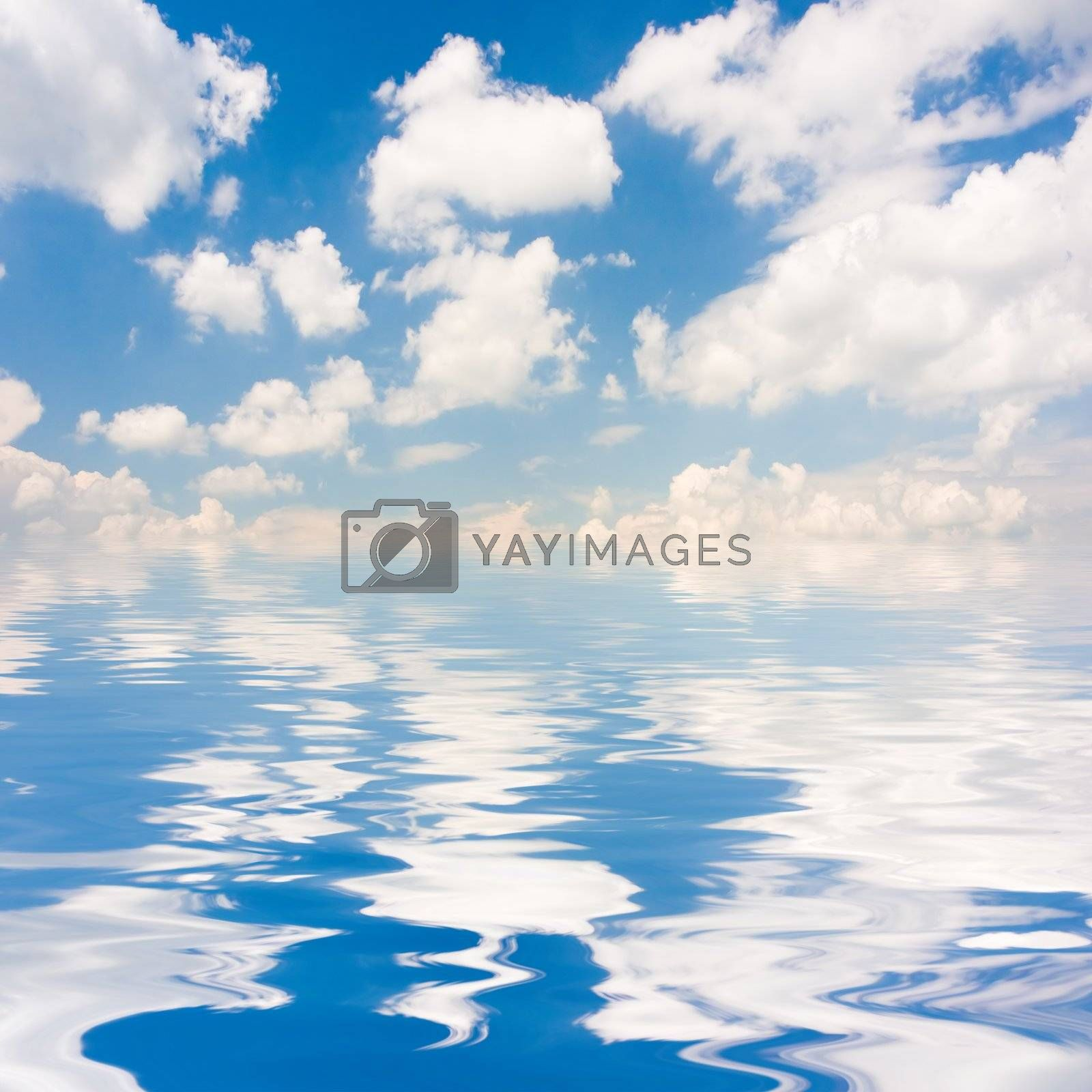 Blue sky with fluffy clouds reflected on water surface.