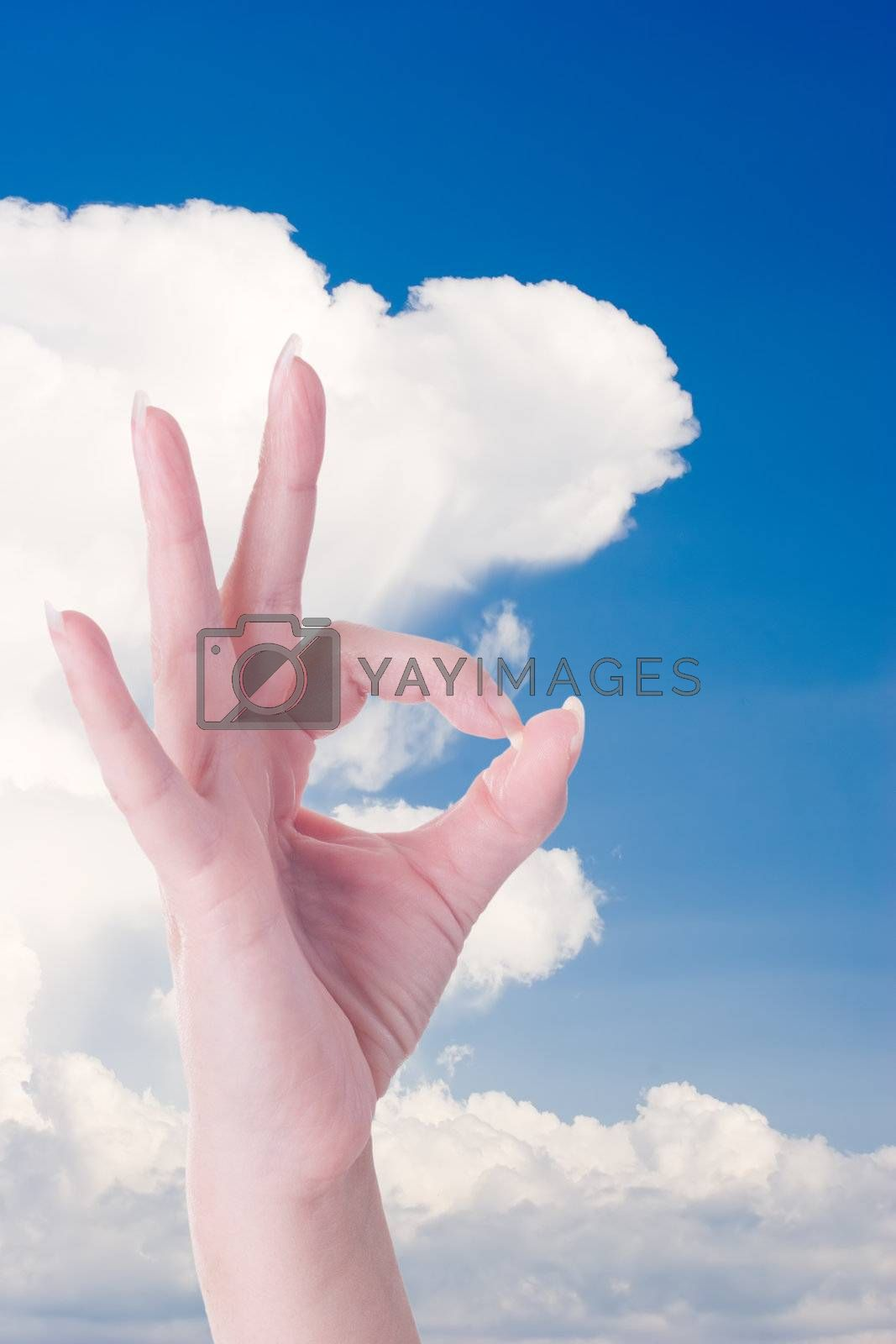Woman hand doing an ok gesture against blue sky with cloud.