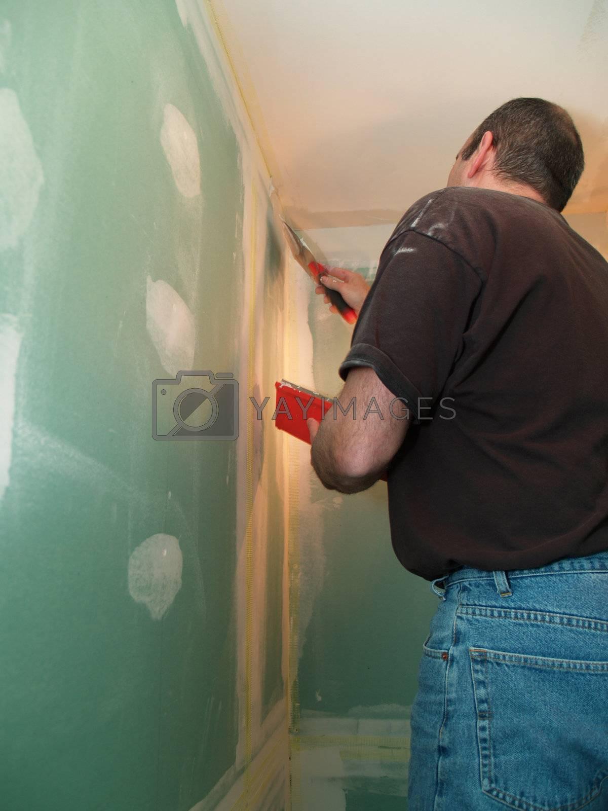 man spackling new drywall in a bathroom