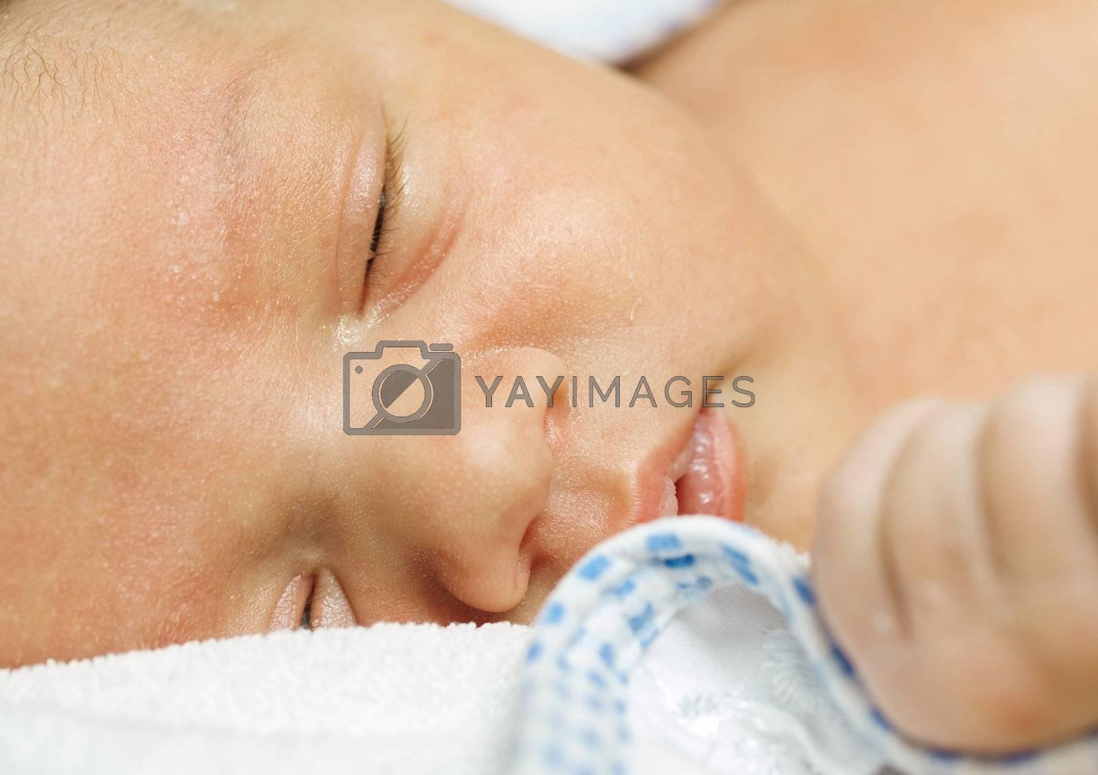 new-born baby sleeping on a towel