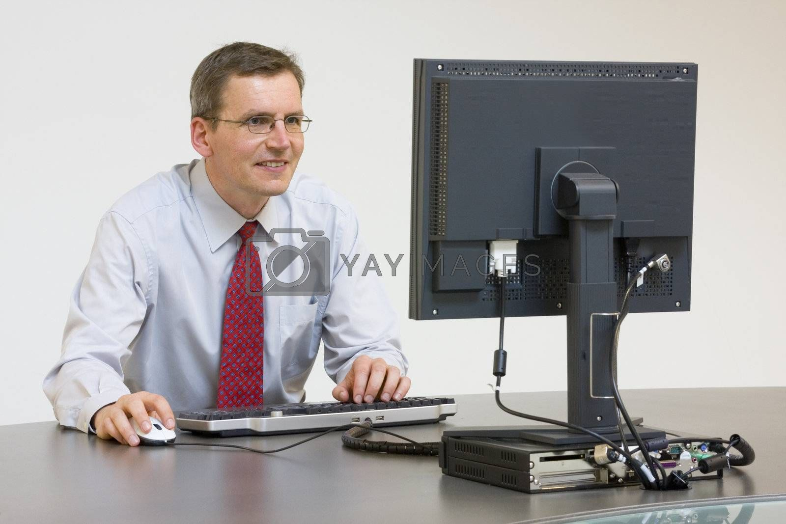 Smiling businessman working with computer in an office