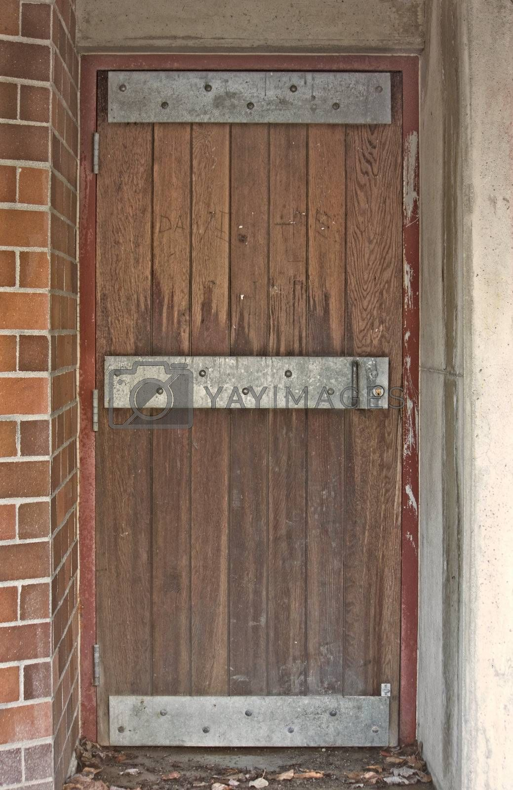 Old Looking Steel Reinforced Door with Wood Boards and Red Brick Wall with mortar.