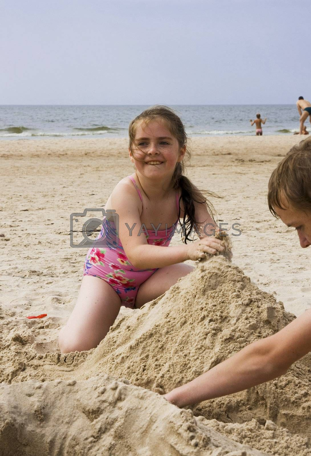 Happy smiling girl playing on beach sand. Lithuania, coast of Baltic sea