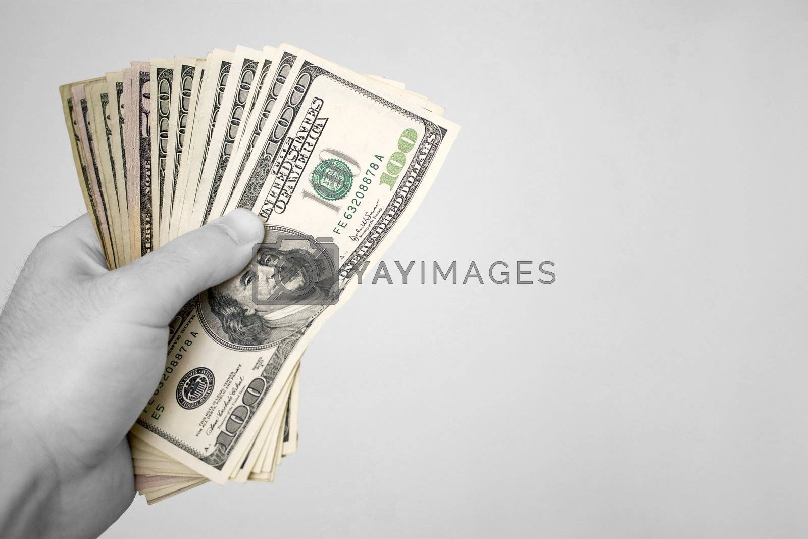 A handful of fanned out cash. The money has selective color, and the rest of the image is in black and white.