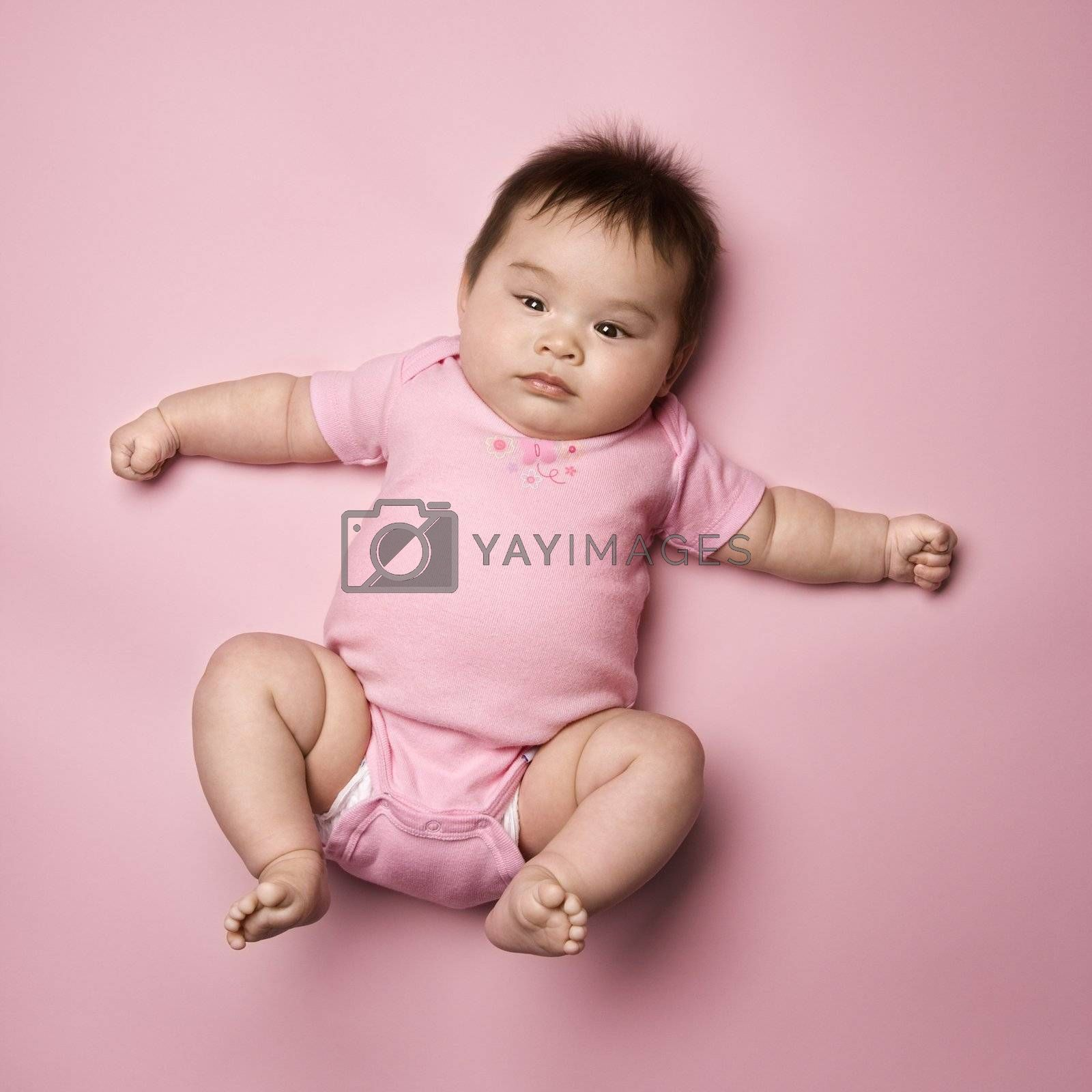 Asian baby lying on back lookin up at viewer with arms out to side.