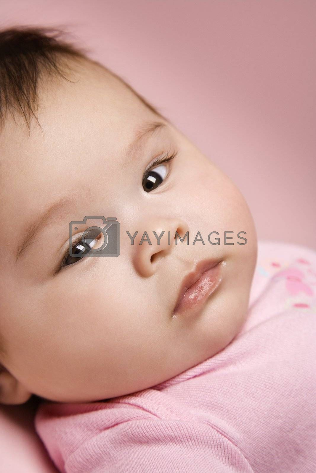 Close up of Asian babys face looking at viewer.
