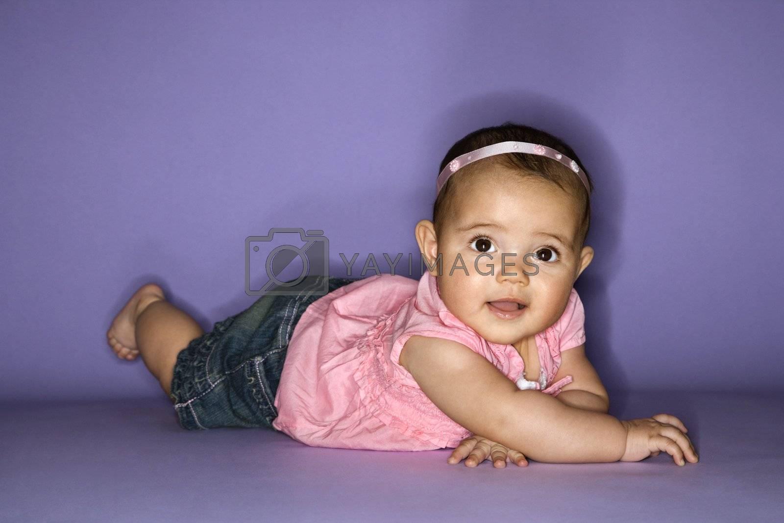Hispanic female baby lying on stomach.