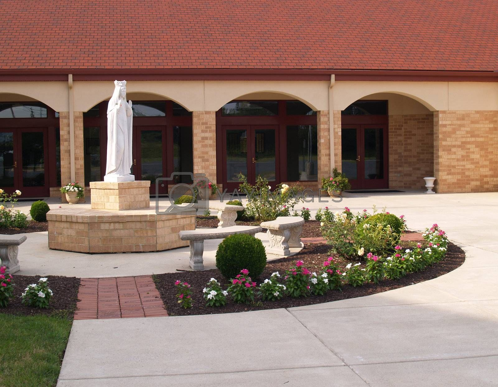 a religious statue outside a brick church