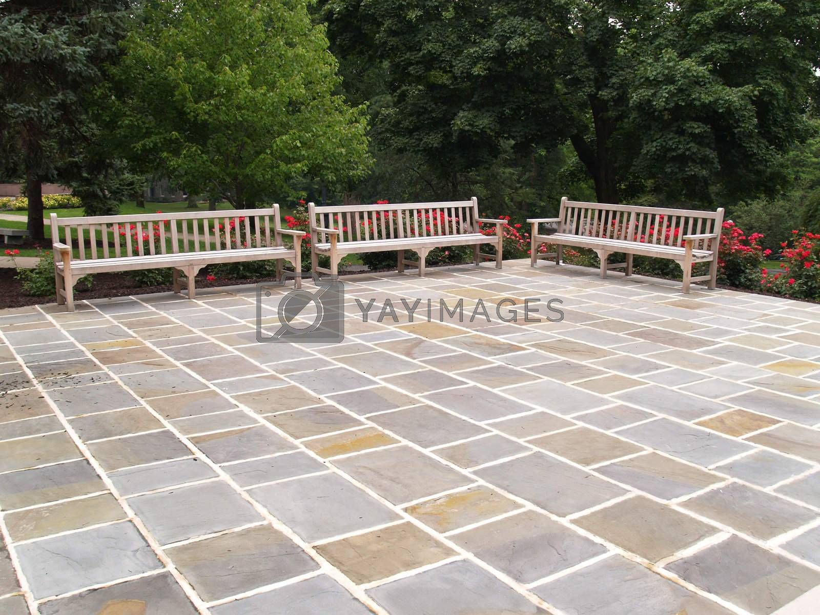 three empty wood benches by a stone patio