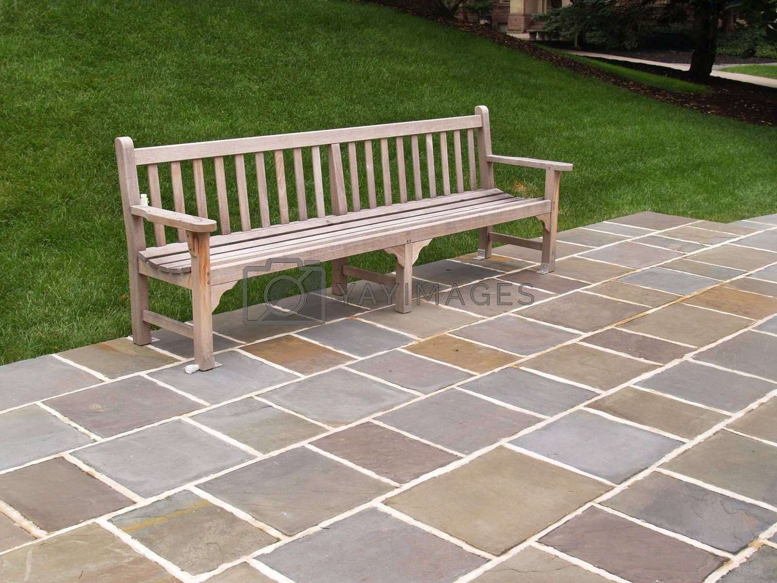 one empty wood bench by a stone patio