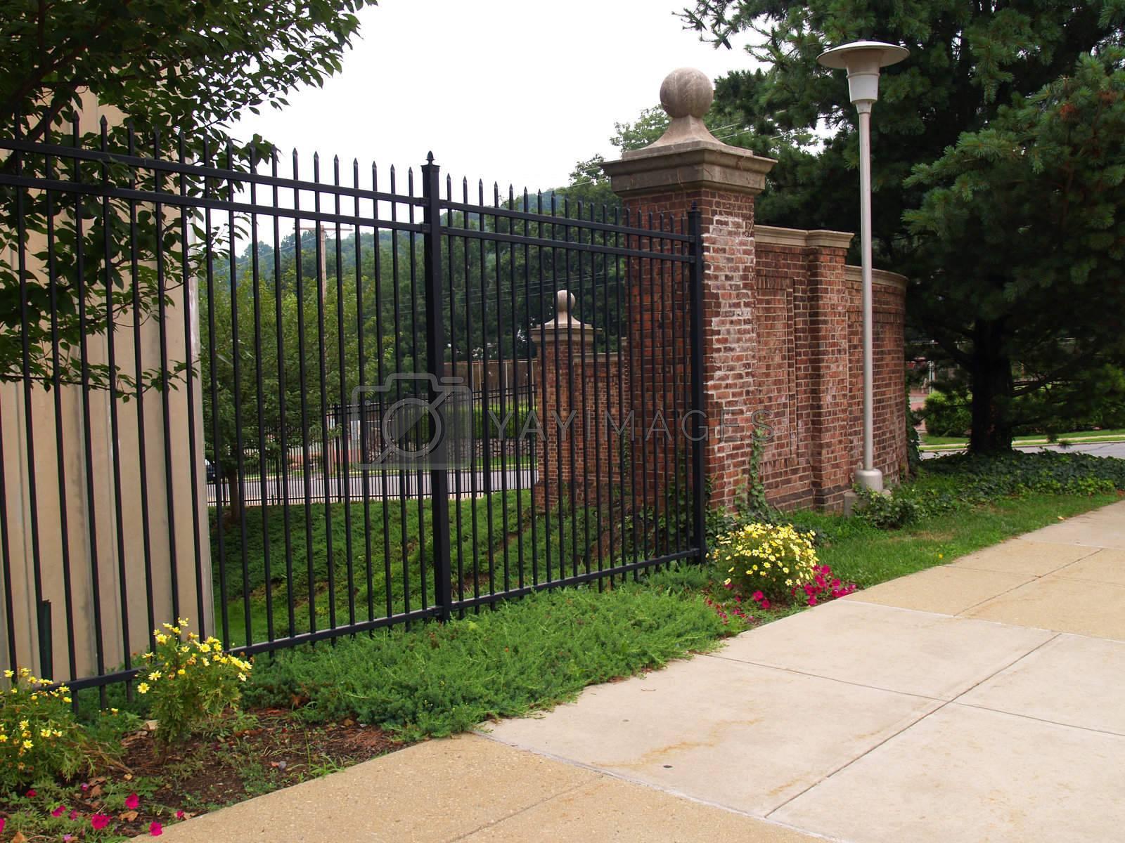 tall black iron fence and a brick cornerpiece