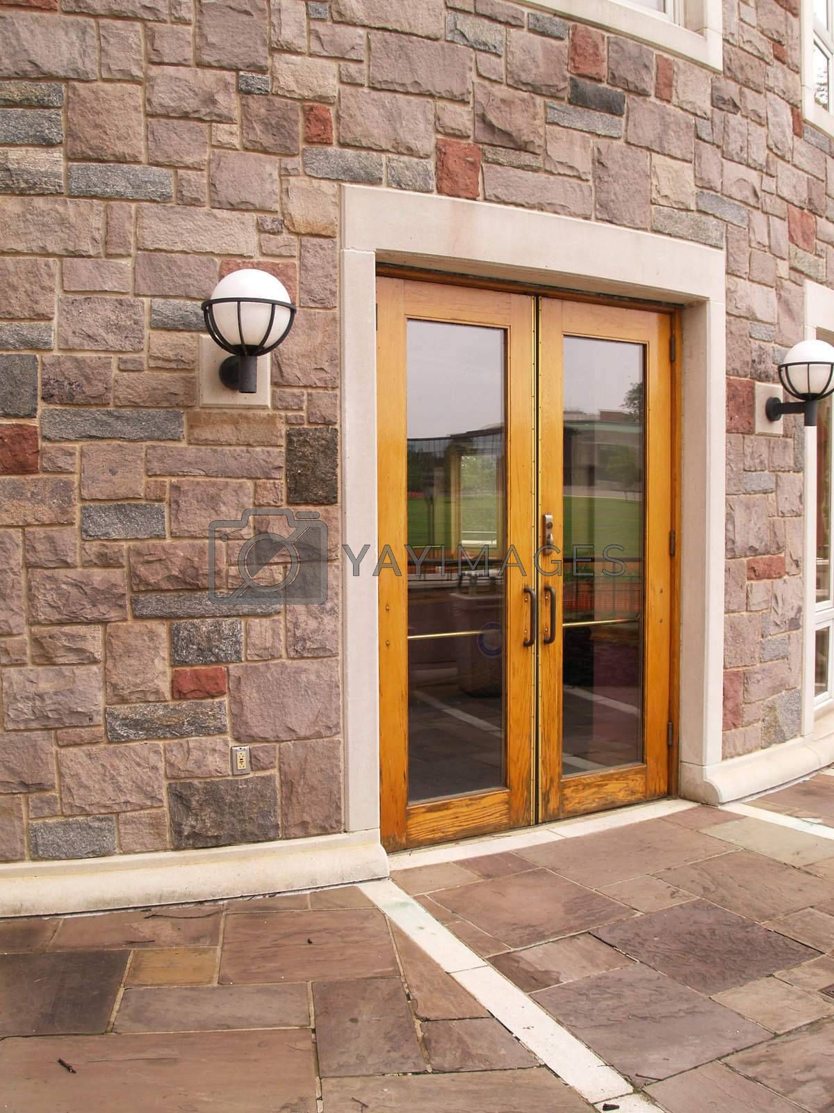 double wood doors by a stone building