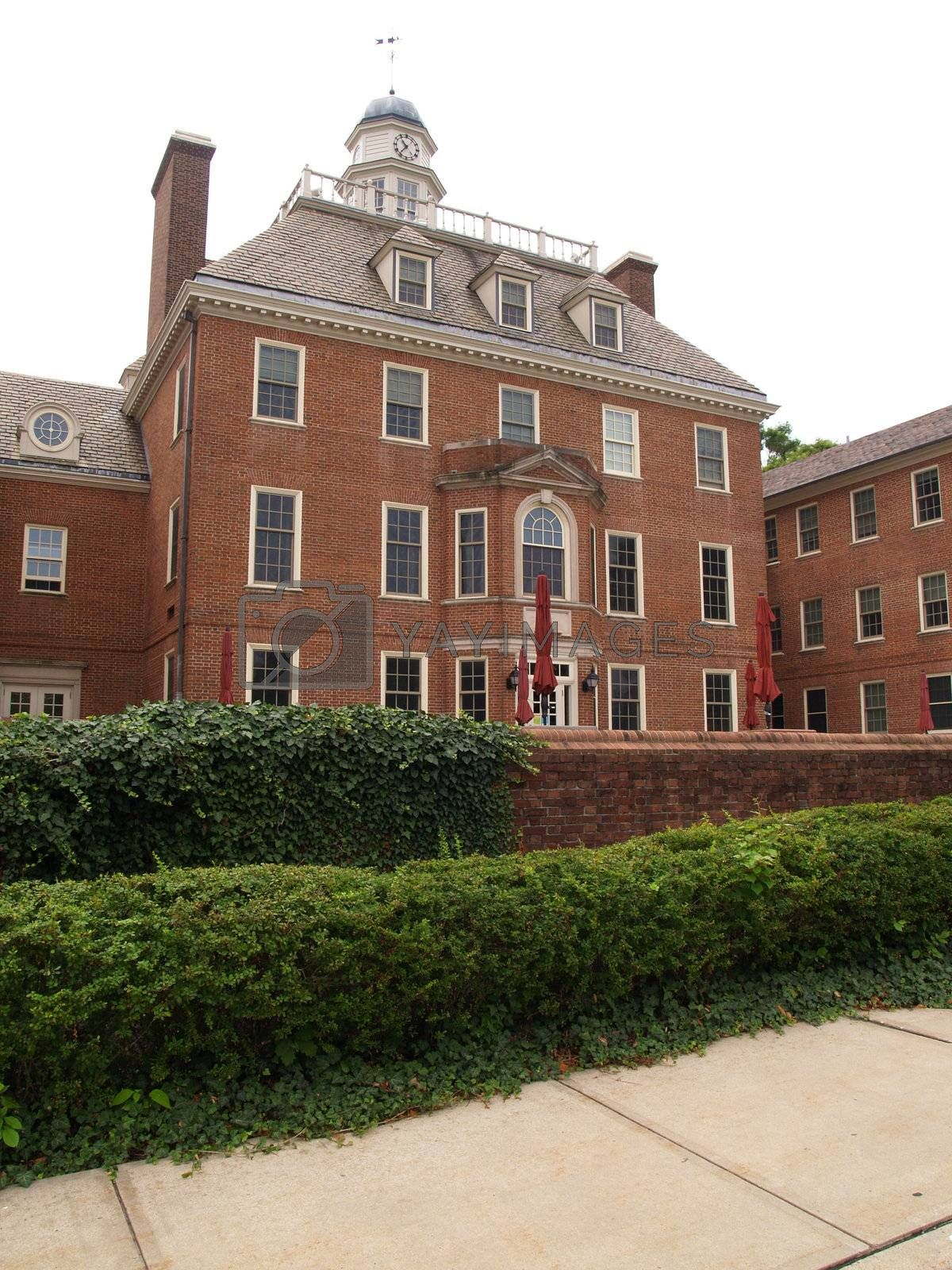 colonial style red brick building with brick wall and ivy