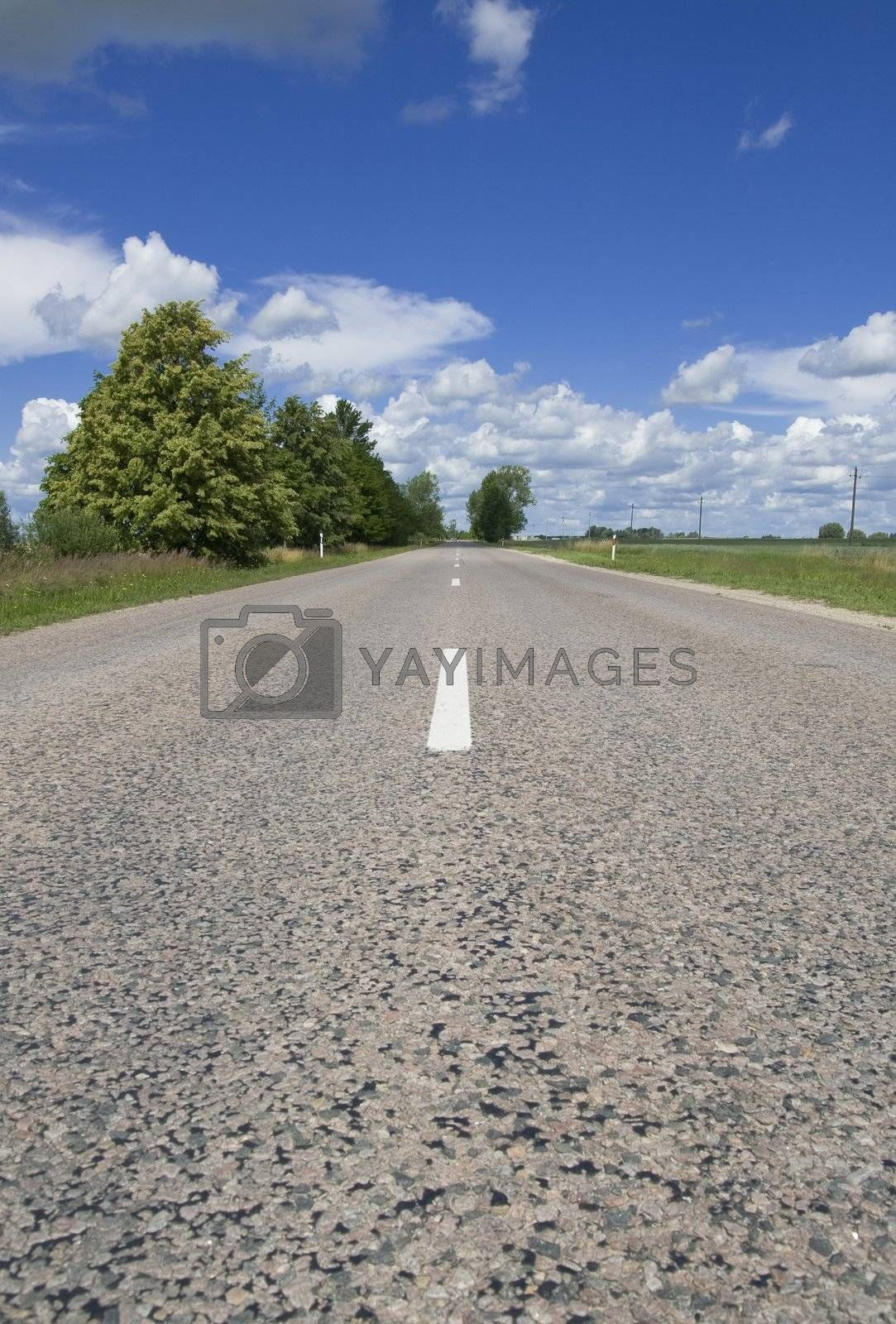 Summer landscape - empty highway, clouds and the blue sky