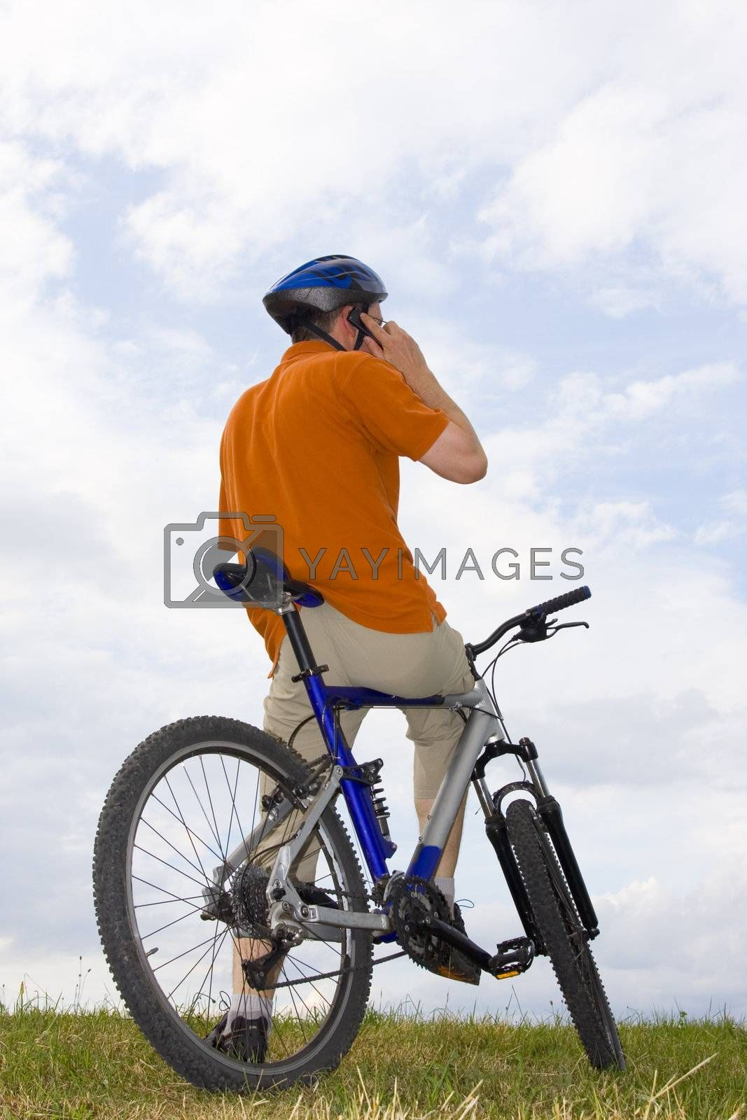 Man with mountain bike on a meadow making a phone call