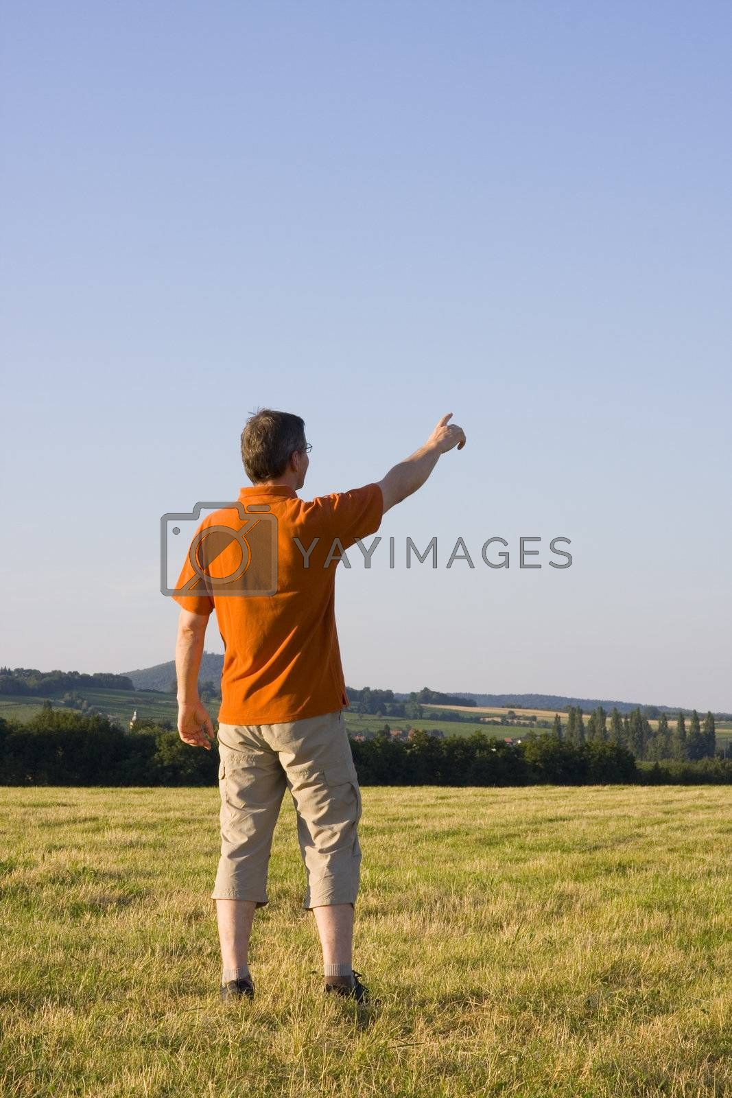 Man pointing with his outstretched arm on a meadow