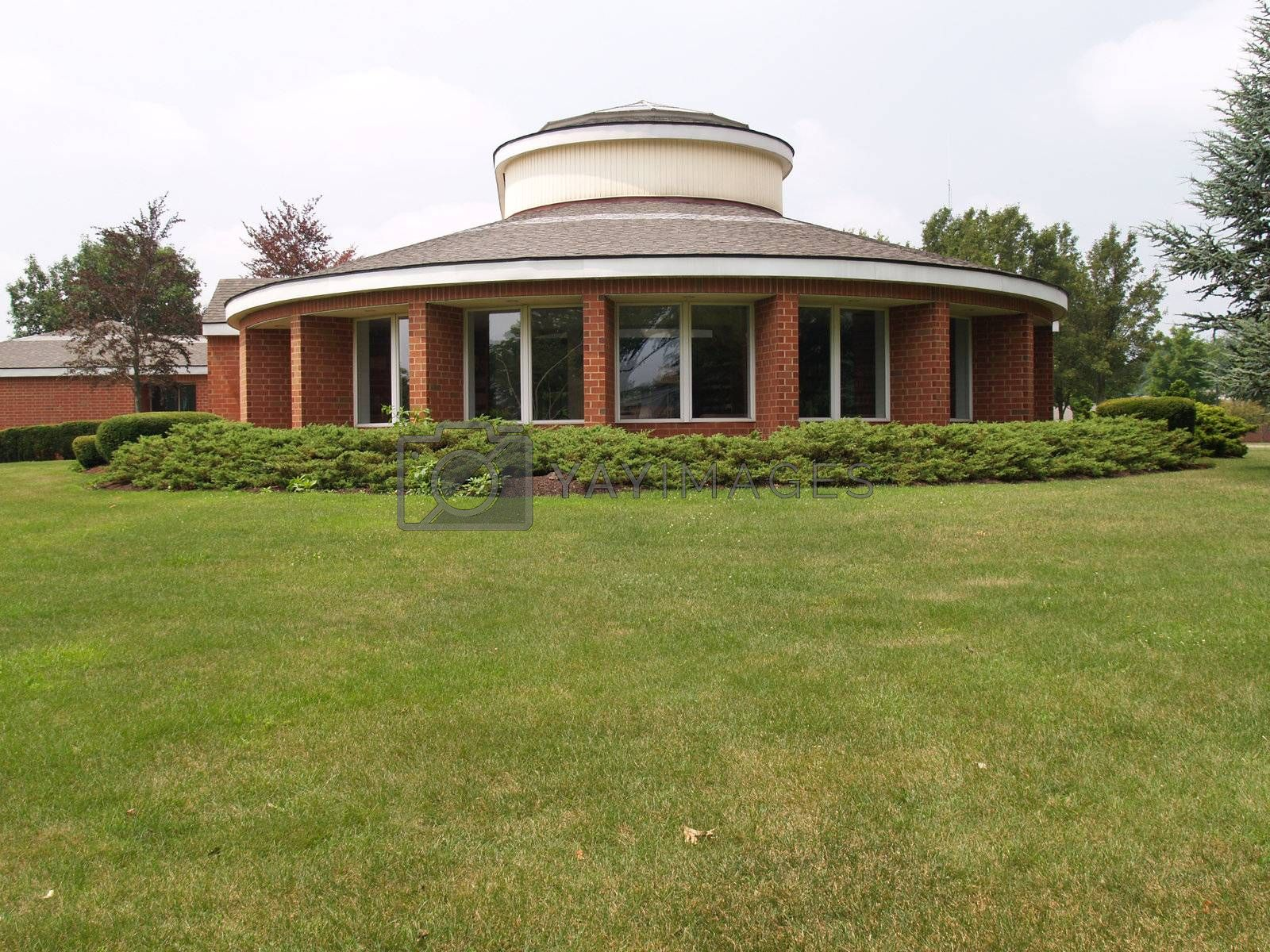 modern round brick building with many windows and green lawn