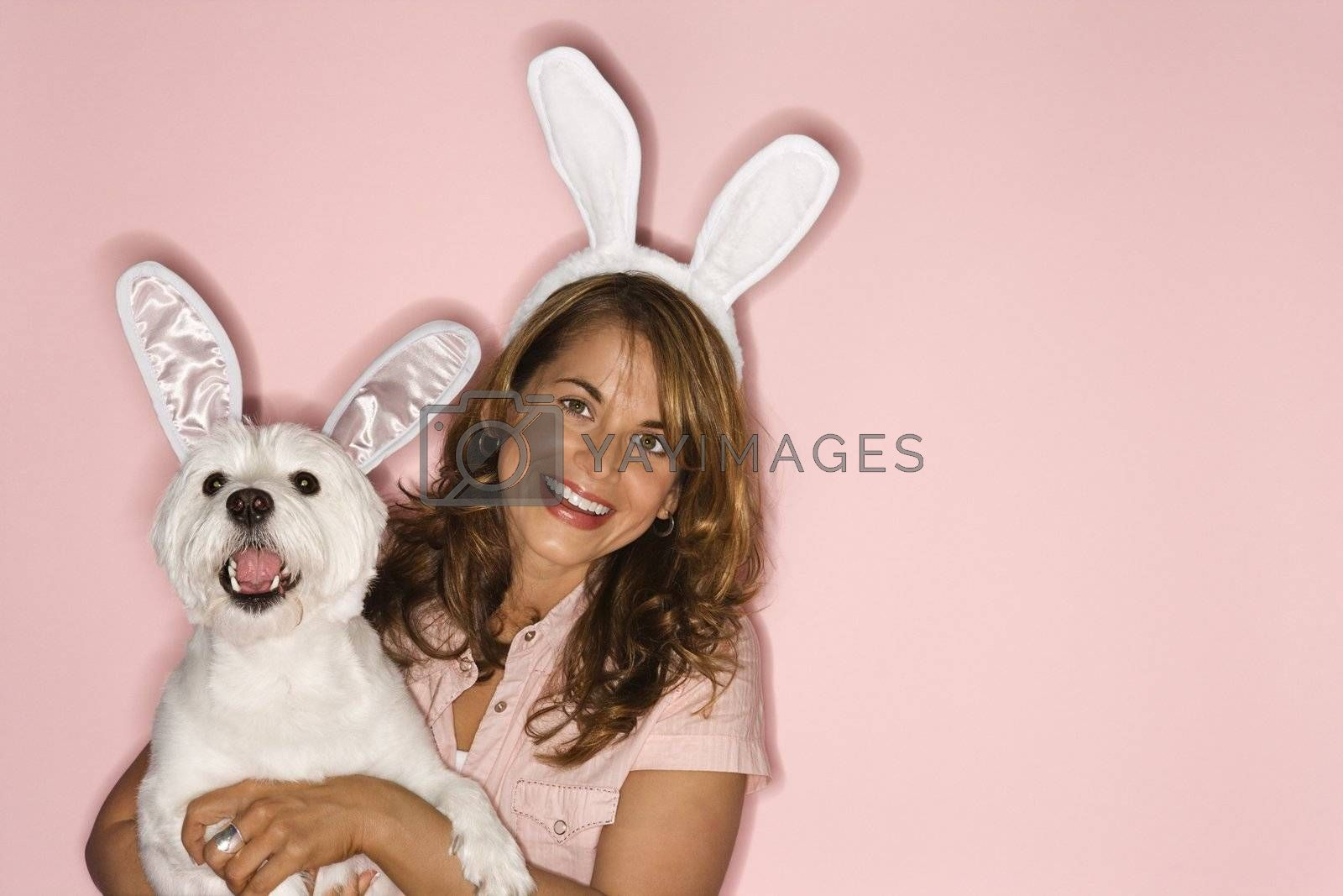 Caucasian prime adult female and white terrier dog wearing rabbit ears.