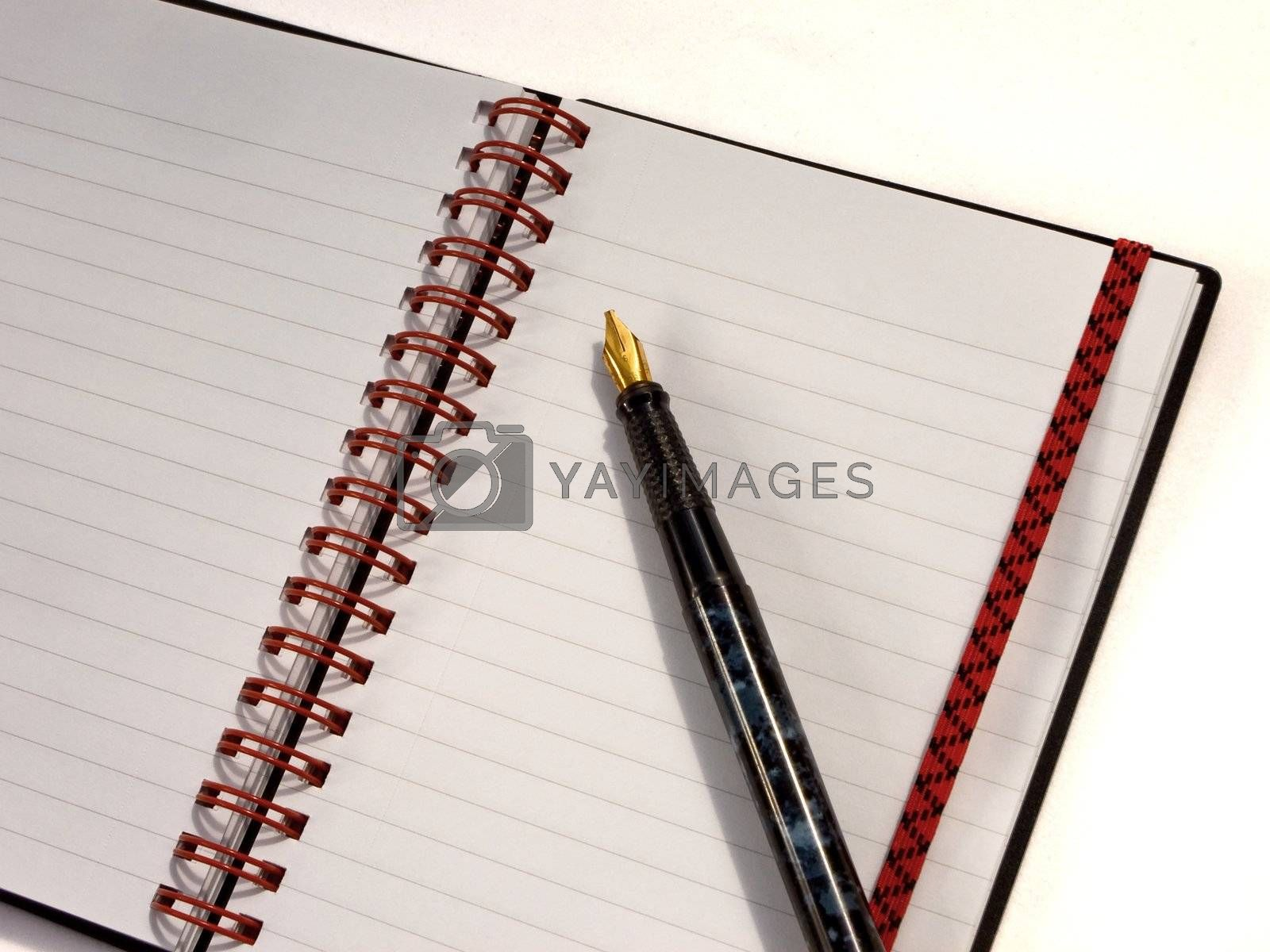 Spiral notebook open with pen on a white background.