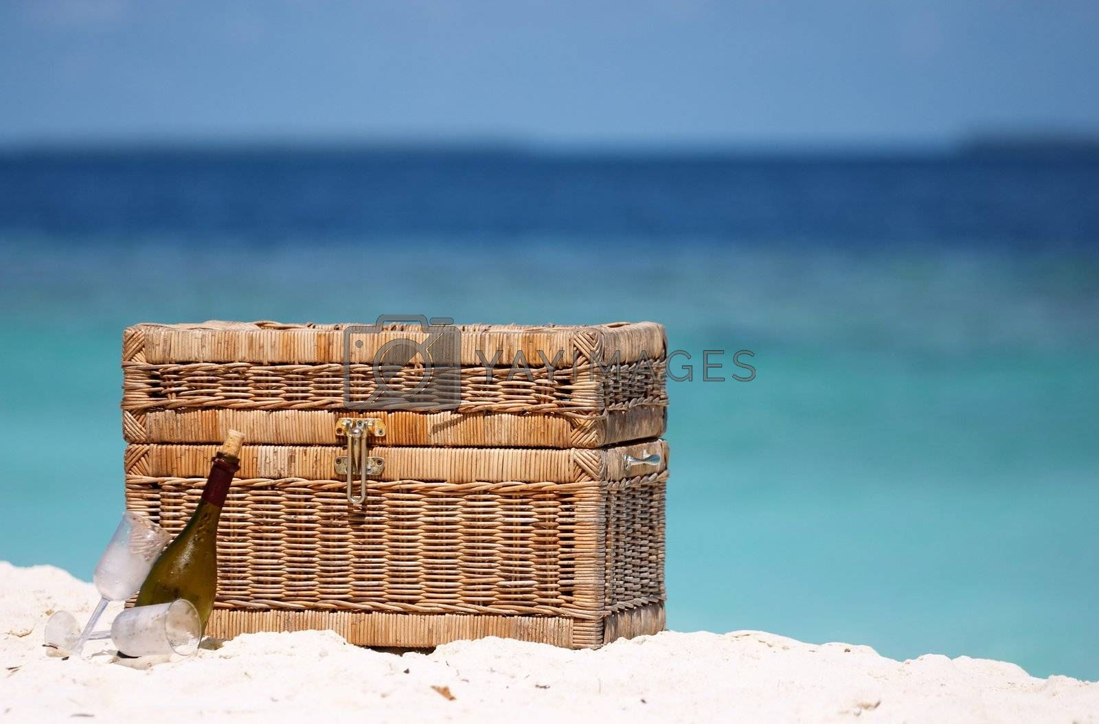 Picnic basket, wine and two wine glasses on the white sand beach