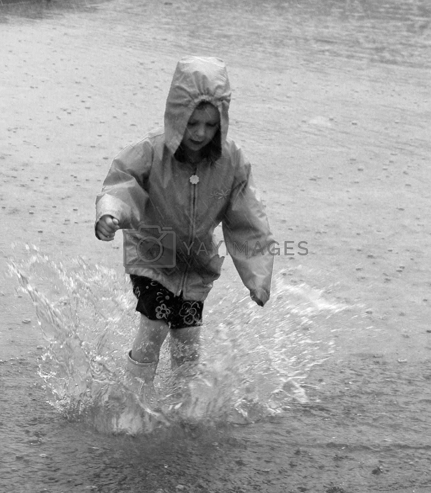 Child Jumping in Rainy Street