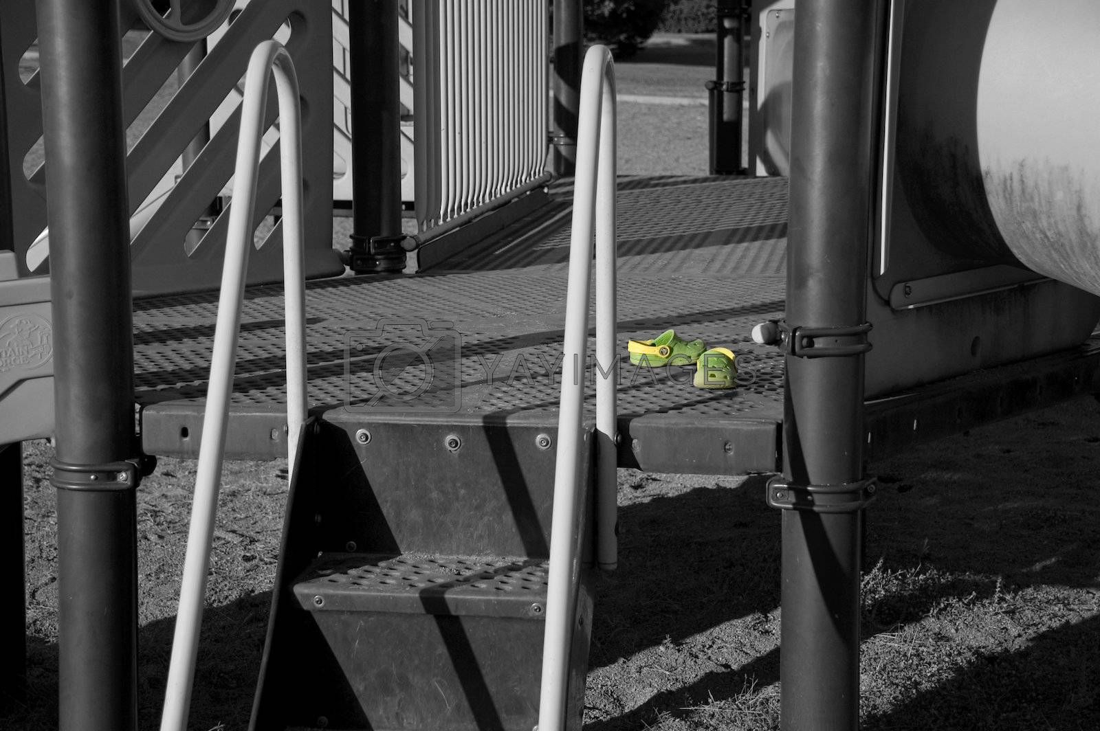 A pair of green kid's shoes on the playground, only the shoes are color.