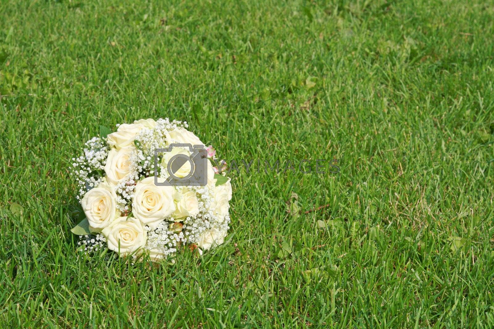 Wedding bouquet from white roses on a green grass