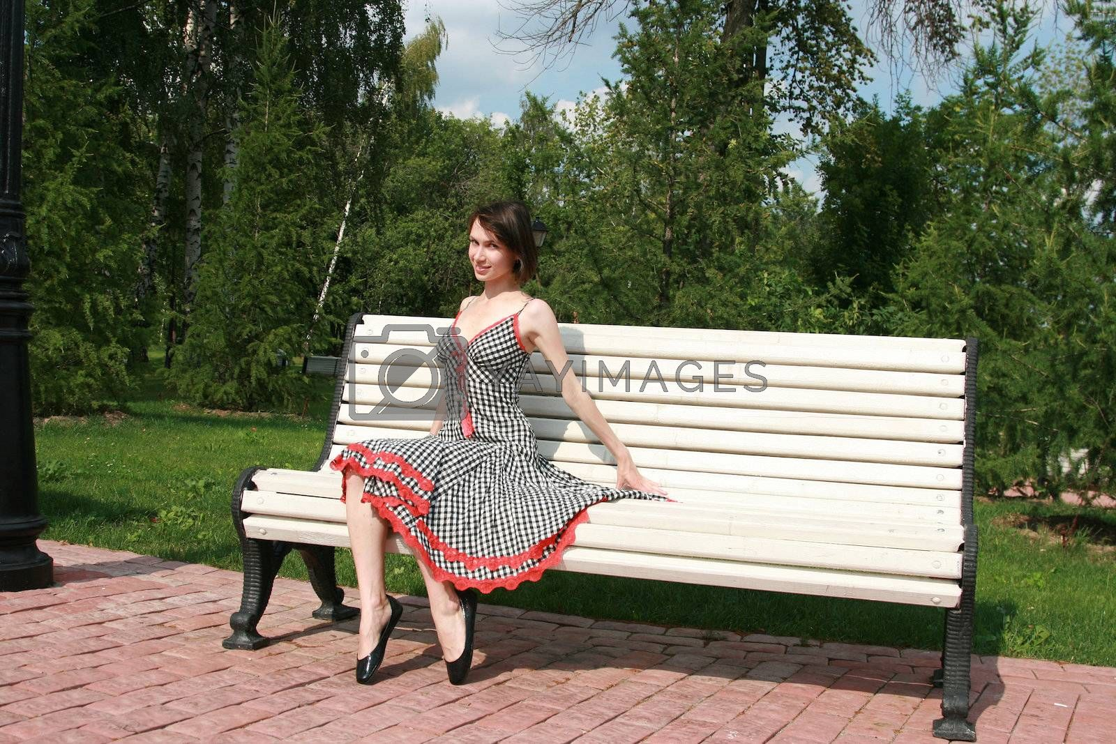 The girl sits on a bench and coquettishly poses