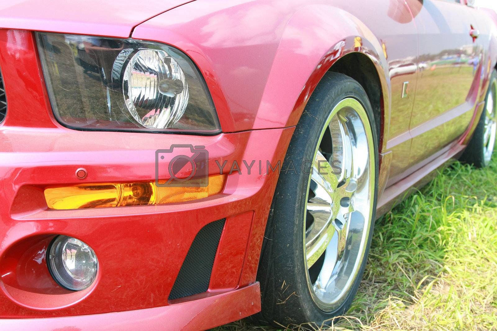 Fragment of the red sports car costing on the ground