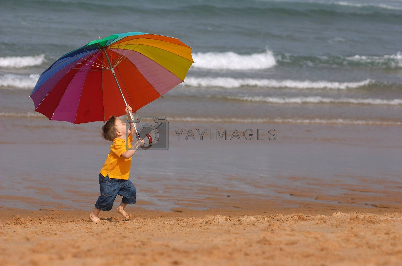 Do not depend on weather conditions. Cute small boy with big brightly colored umbrella having fun on the beach