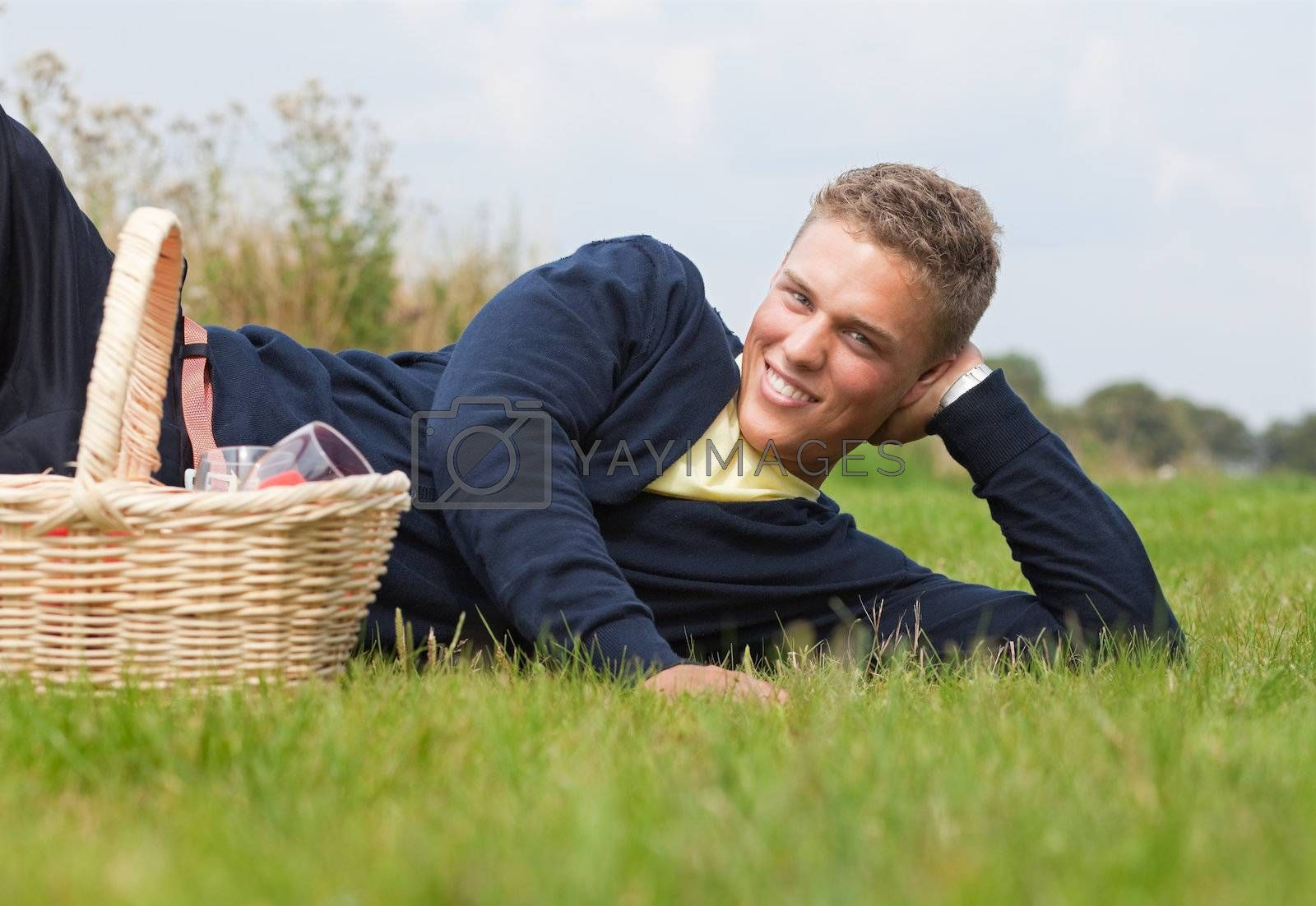 Young handsome blond lying on the grass with picnic basket