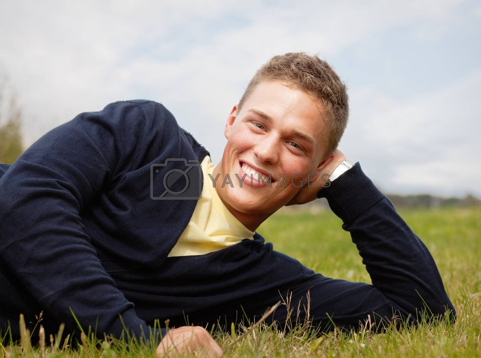 Happy young blond man lying on the grass