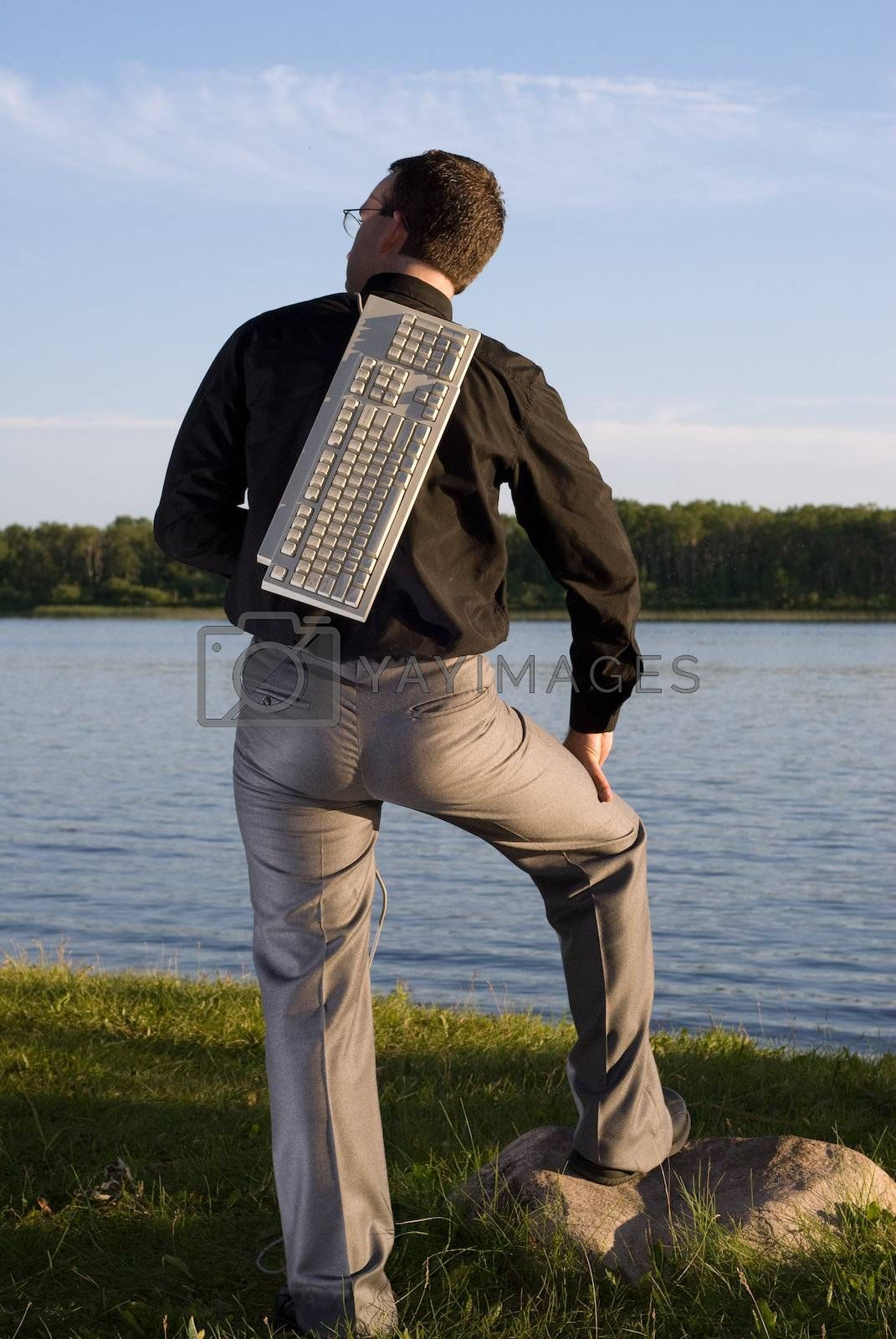 A young businessman holding a keyboard over his back