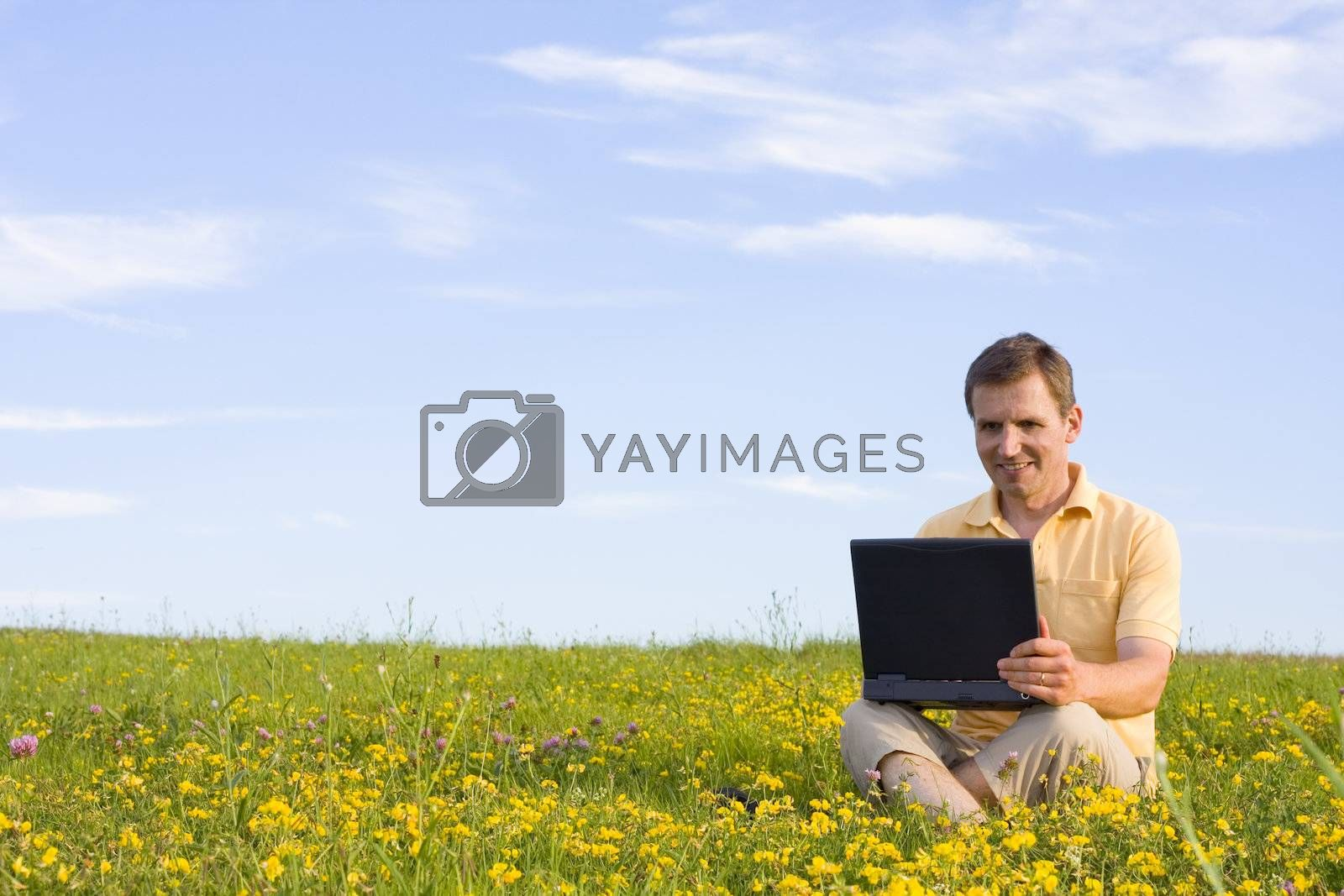 Royalty free image of Man sitting with laptop computer in a meadow by ArtmannWitte