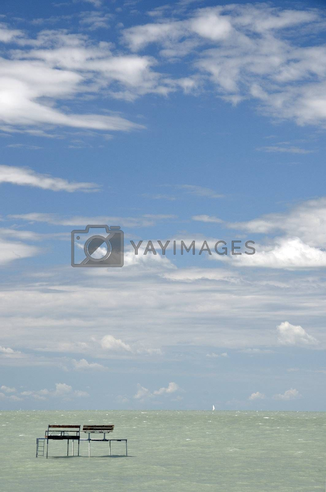 Fishing pier against blue sky with clouds